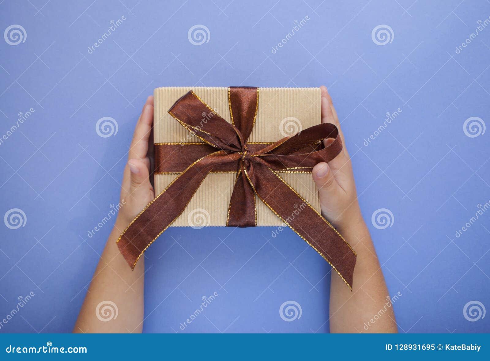 在淡色紫色背景的礼物盒在儿童` s手上