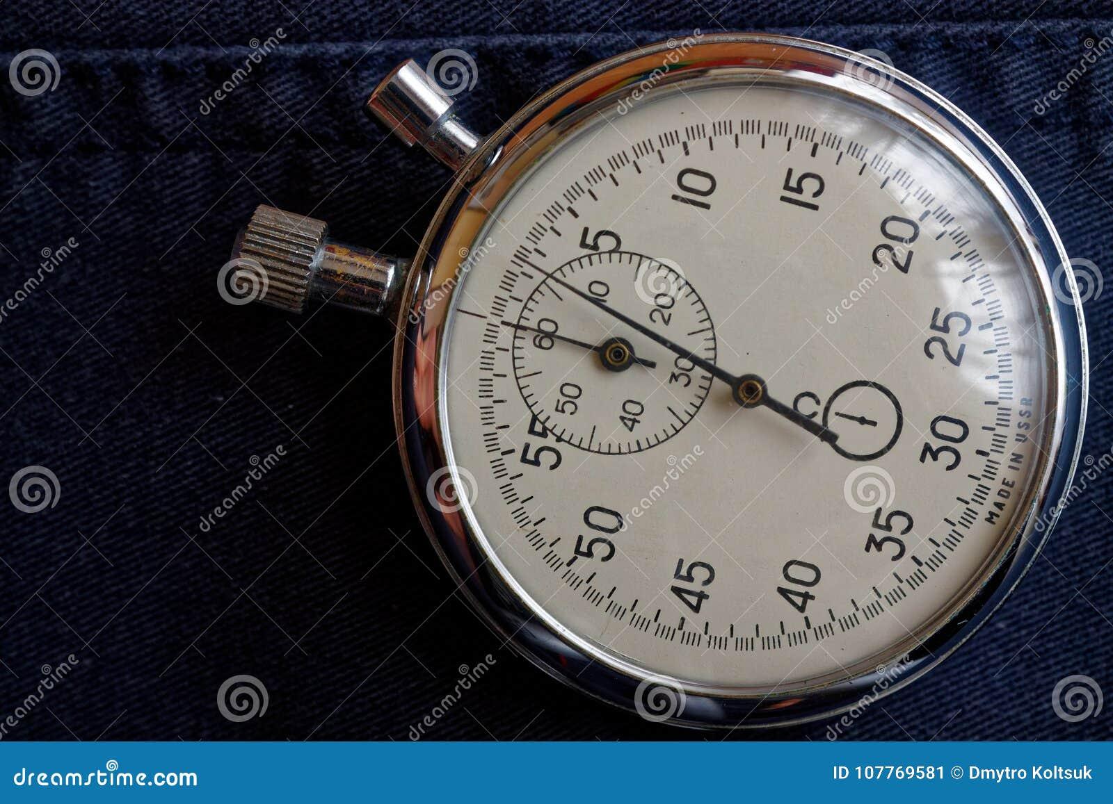 在深蓝牛仔裤背景,价值措施时间、老时钟箭头分钟和第二个准确性定时器纪录的秒表