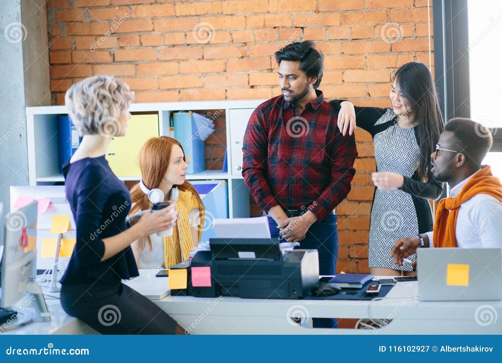 在混合的族种办公室工作者中的交谈便衣的