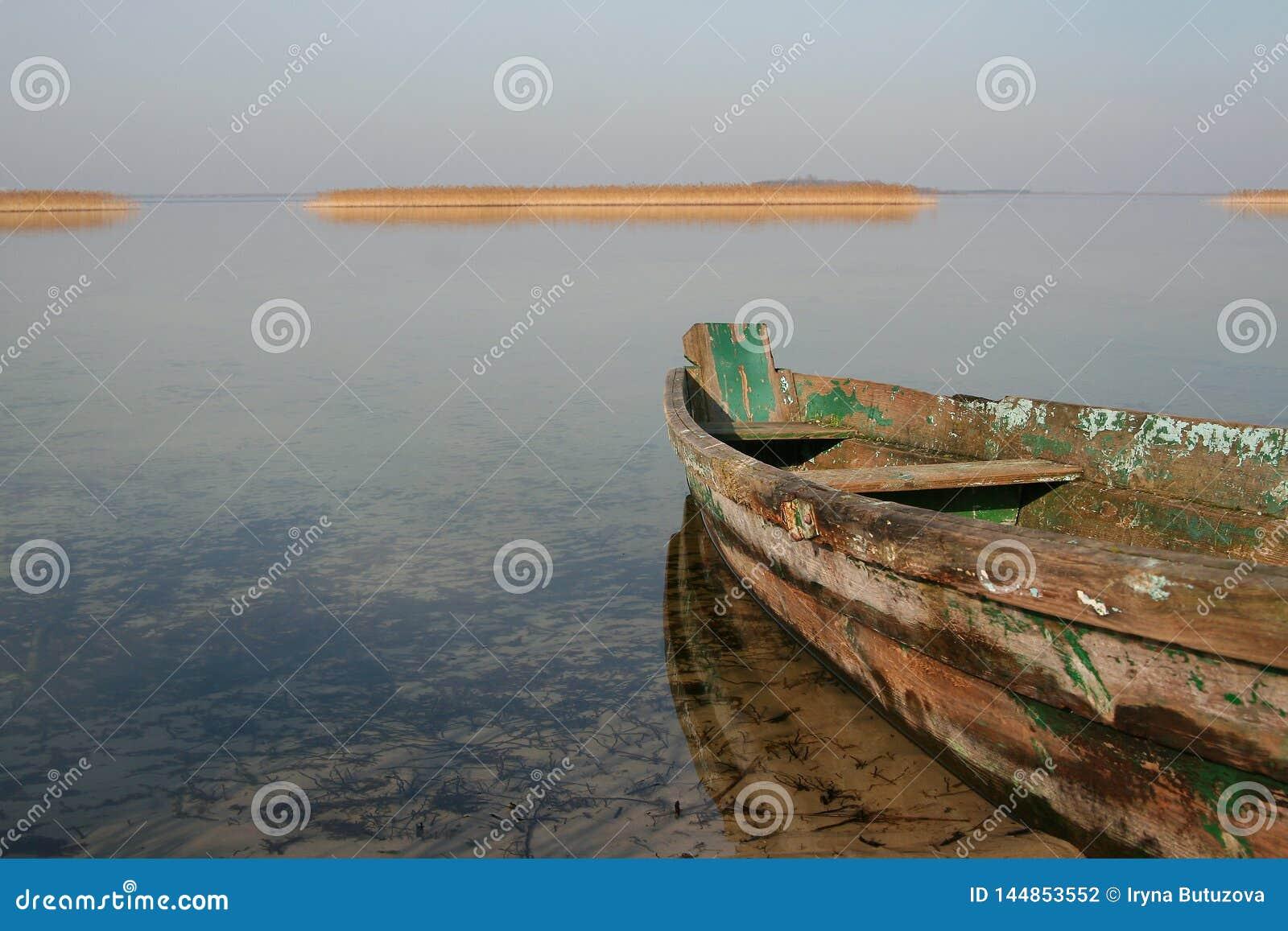 在清楚的水的老木小船