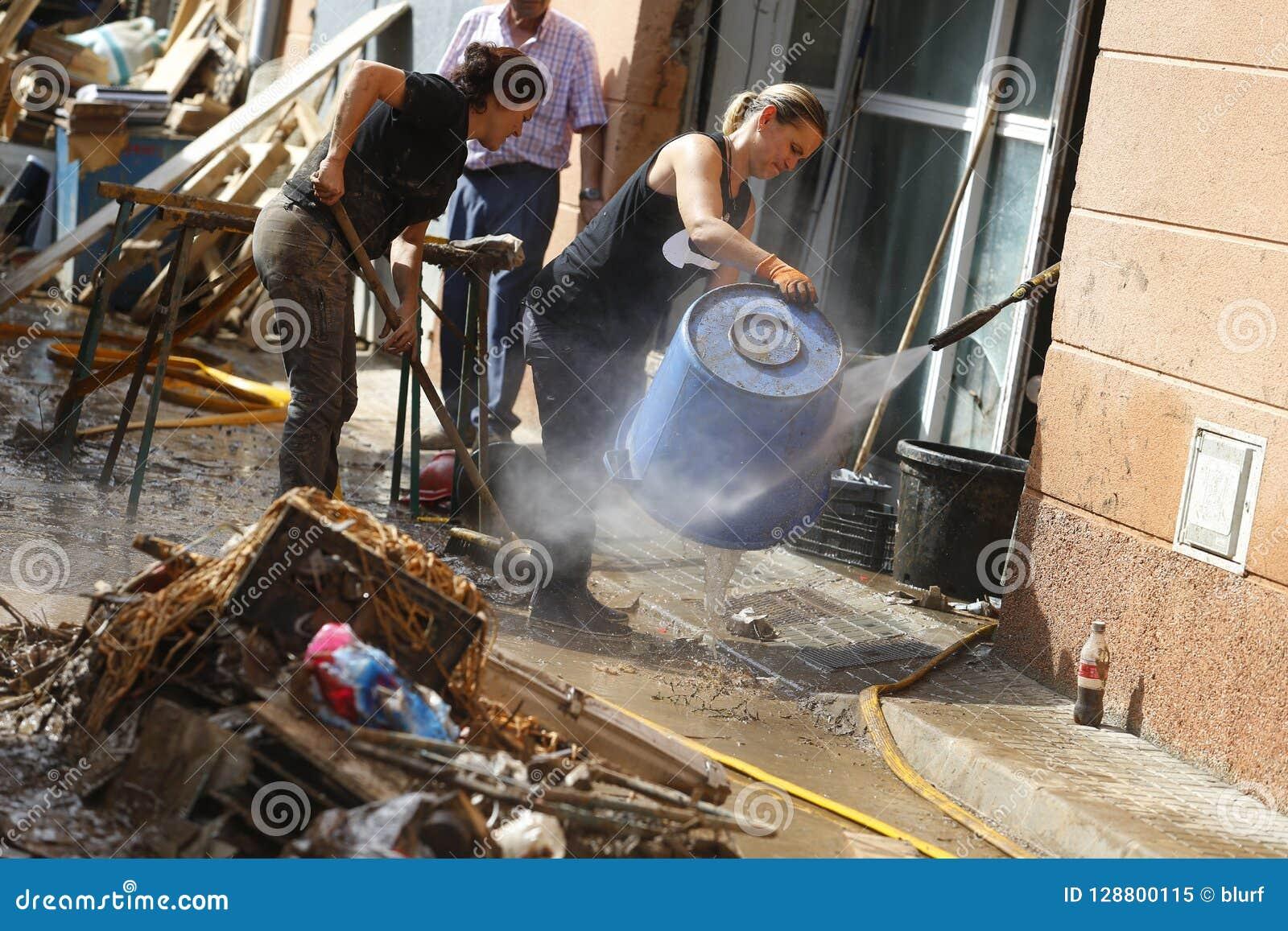 在清洗在洪水以后的村民的细节在圣Llorenc在海岛马略卡