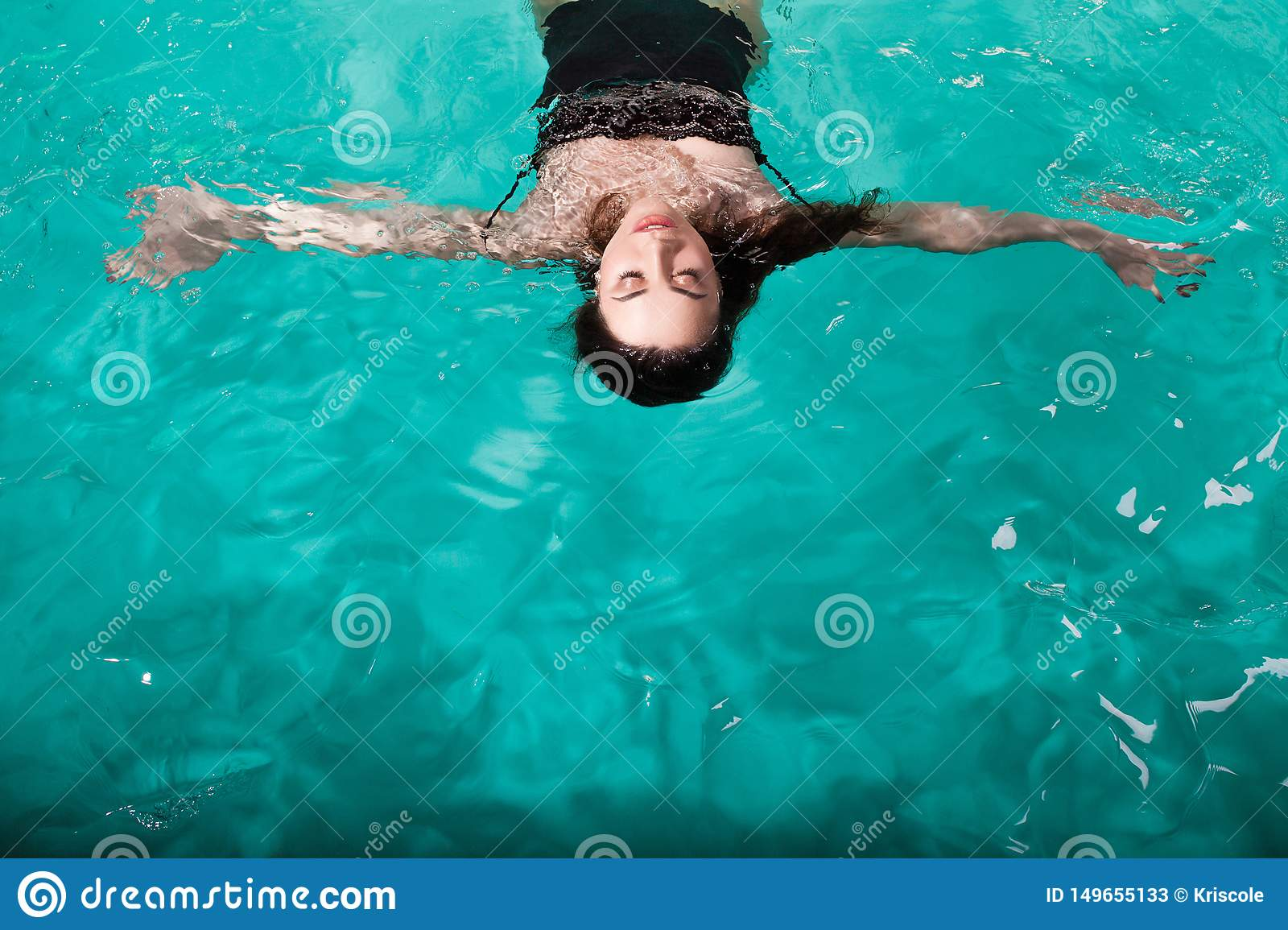 在温泉水池的美好的年轻女人游泳,游泳并且放松