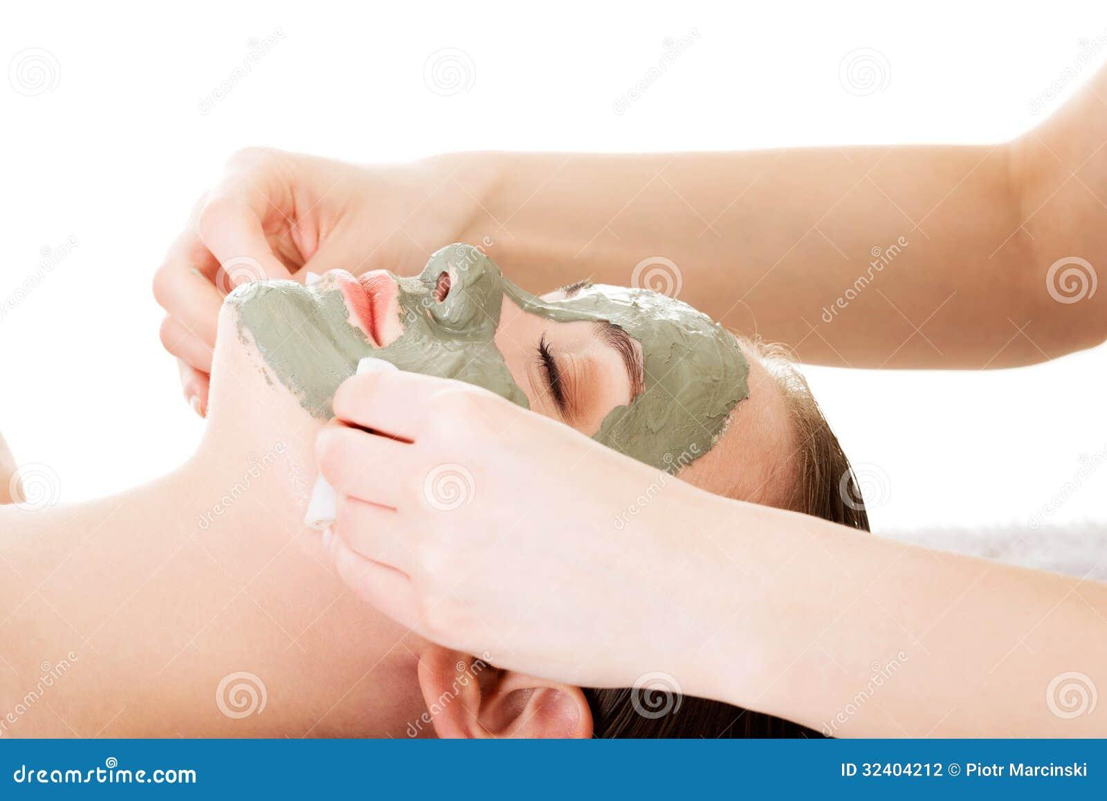 在温泉沙龙的秀丽治疗。有面部黏土面具的妇女。