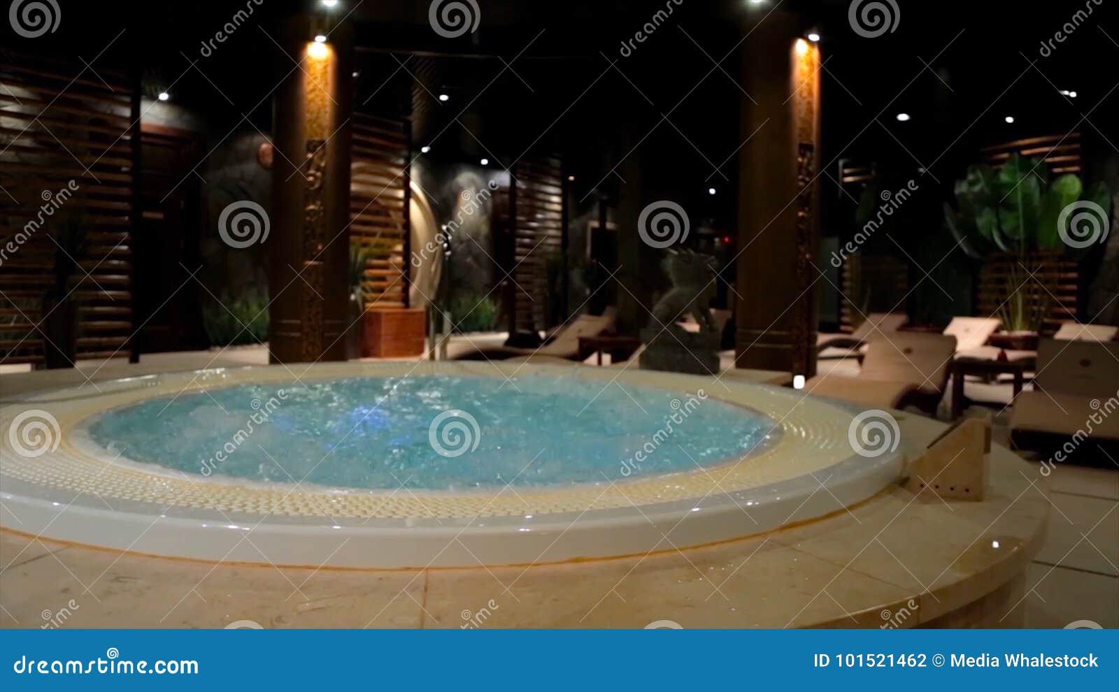在温泉的放松水池与瀑布 与极可意浴缸和游泳池的空的豪华温泉 在蒸汽浴的极可意浴缸 健康