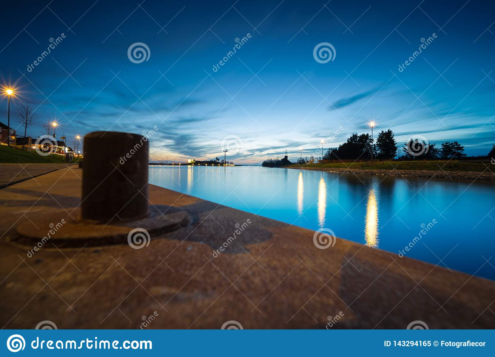 在港口码头的系船柱在微明期间有在江边的一个看法