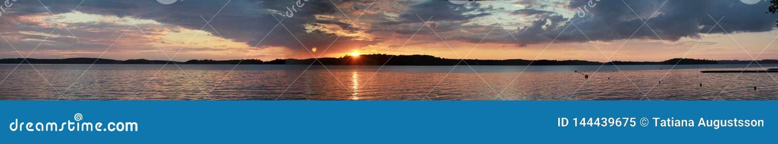 在湖天际风景的日落 在全景河水的视图的黑暗的日落