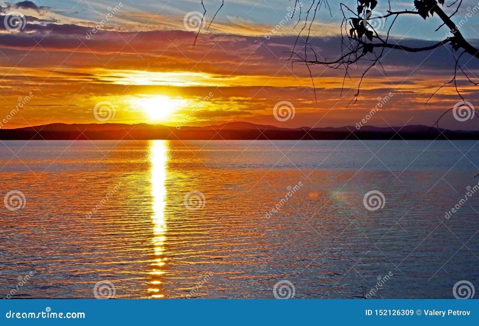 在湖有五颜六色的云彩的,金黄小时的使变暗的日落天空