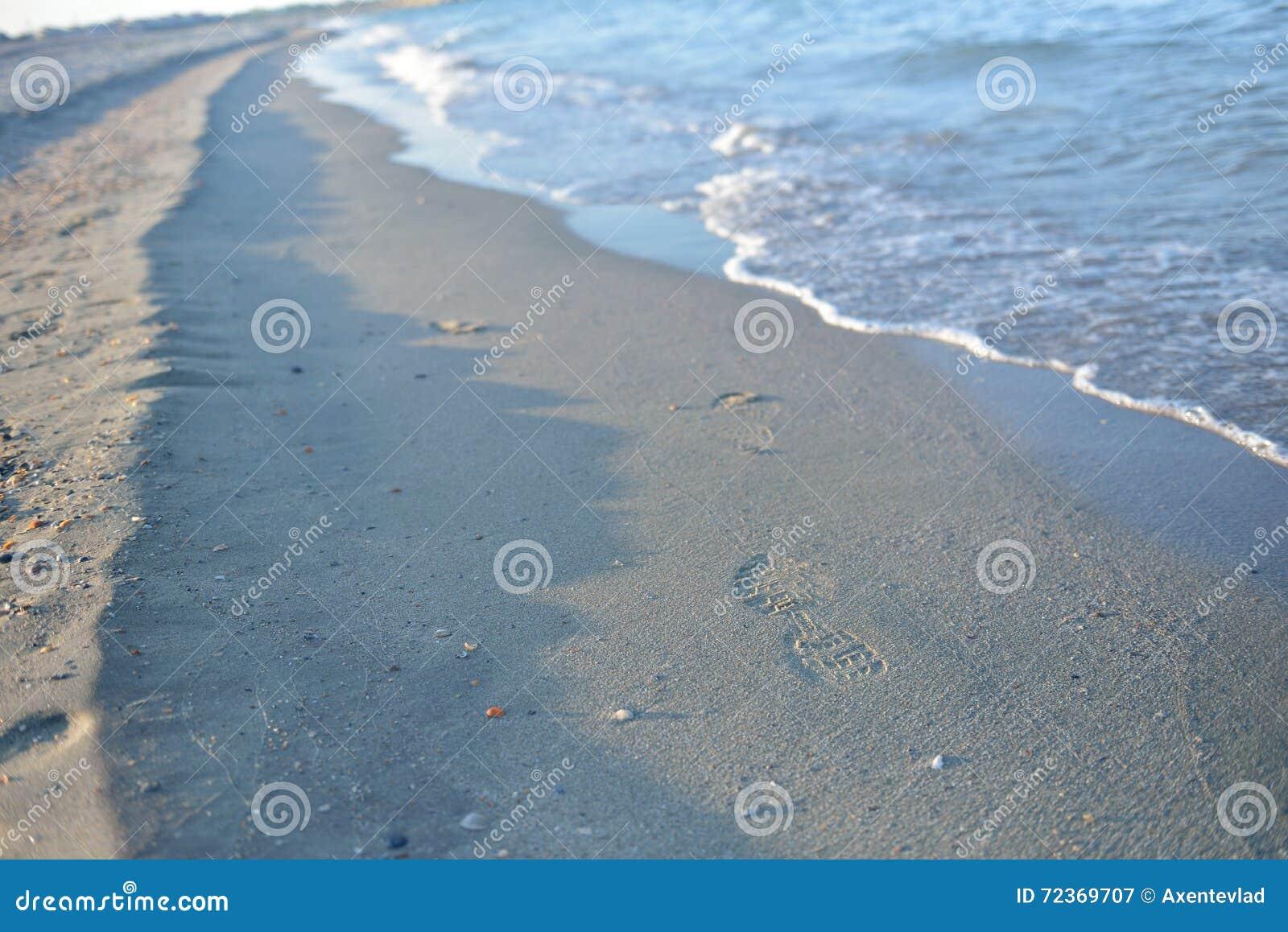 在湿沙子的脚印,在日落的波浪在一个安静的海滩 钛