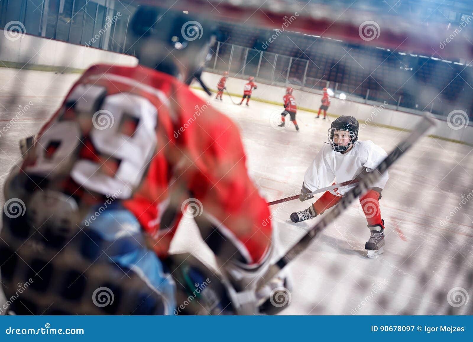 在溜冰场球员的曲棍球比赛攻击守门员