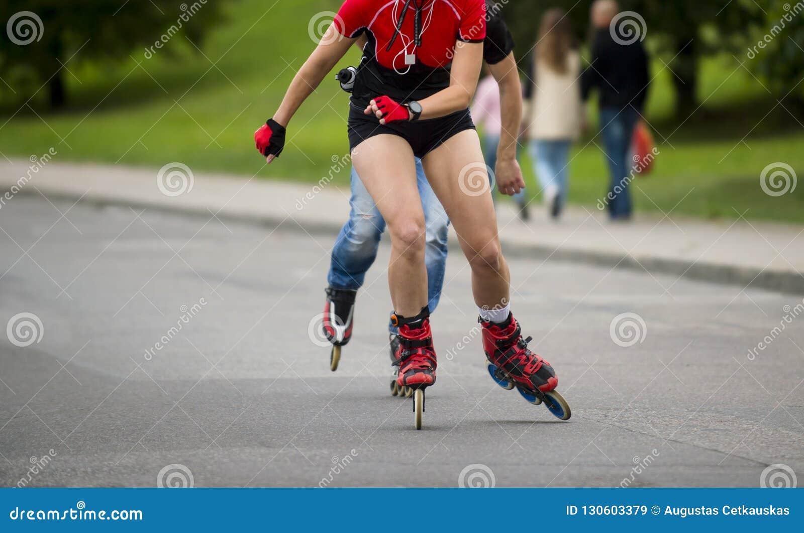 在溜冰鞋的妇女骑马在室外冰鞋公园