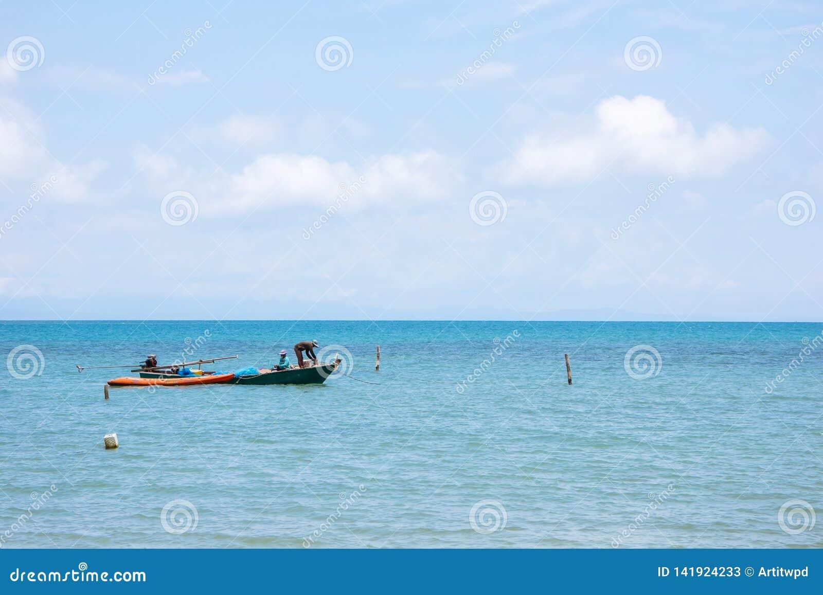 在漂浮在有明亮的天空的海的左边的地方渔夫小船在背景中下午在酸值Mak海岛