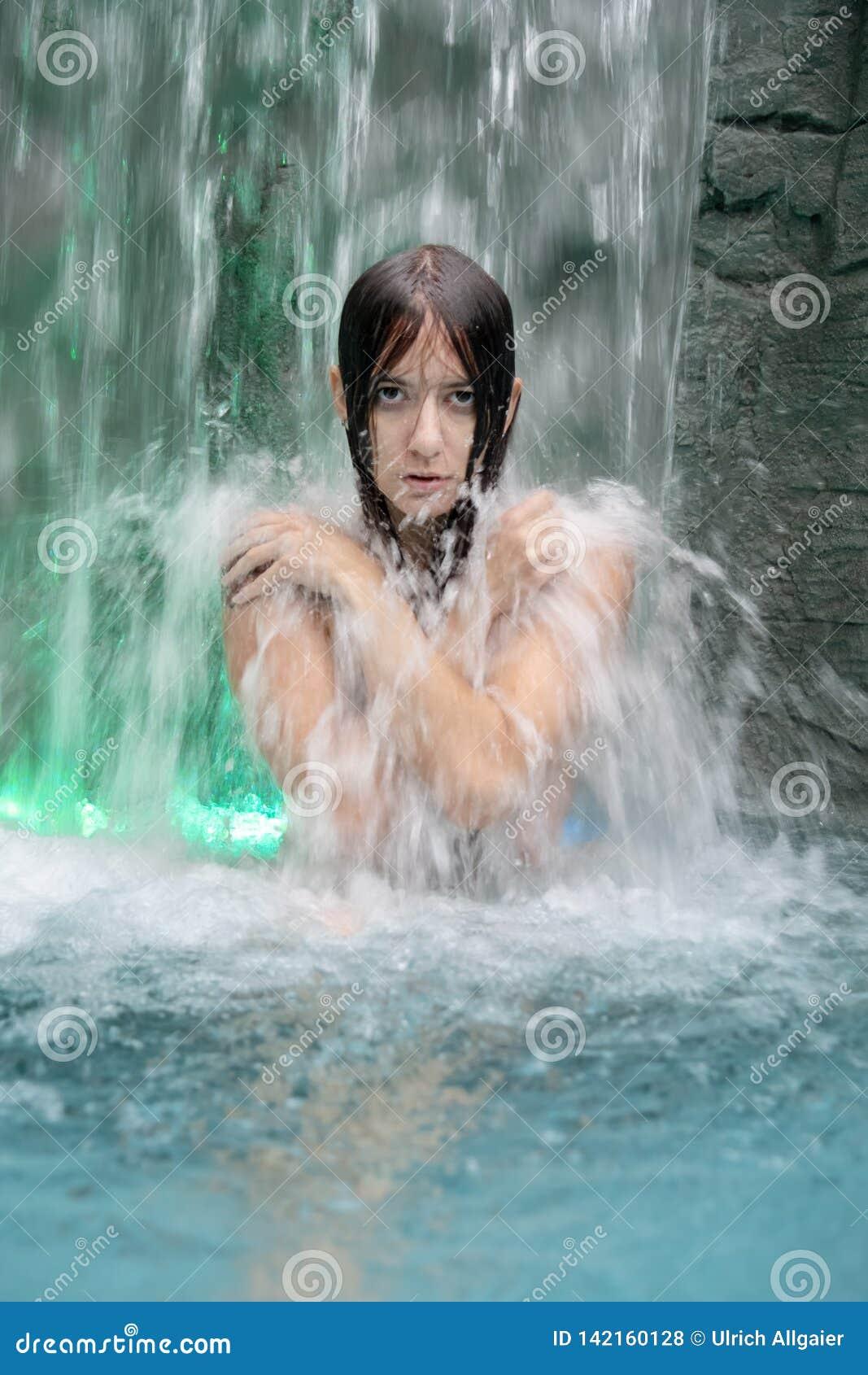在瀑布的飞溅的水的下美丽的年轻赤裸妇女在卫生间里 水池用她报道上身