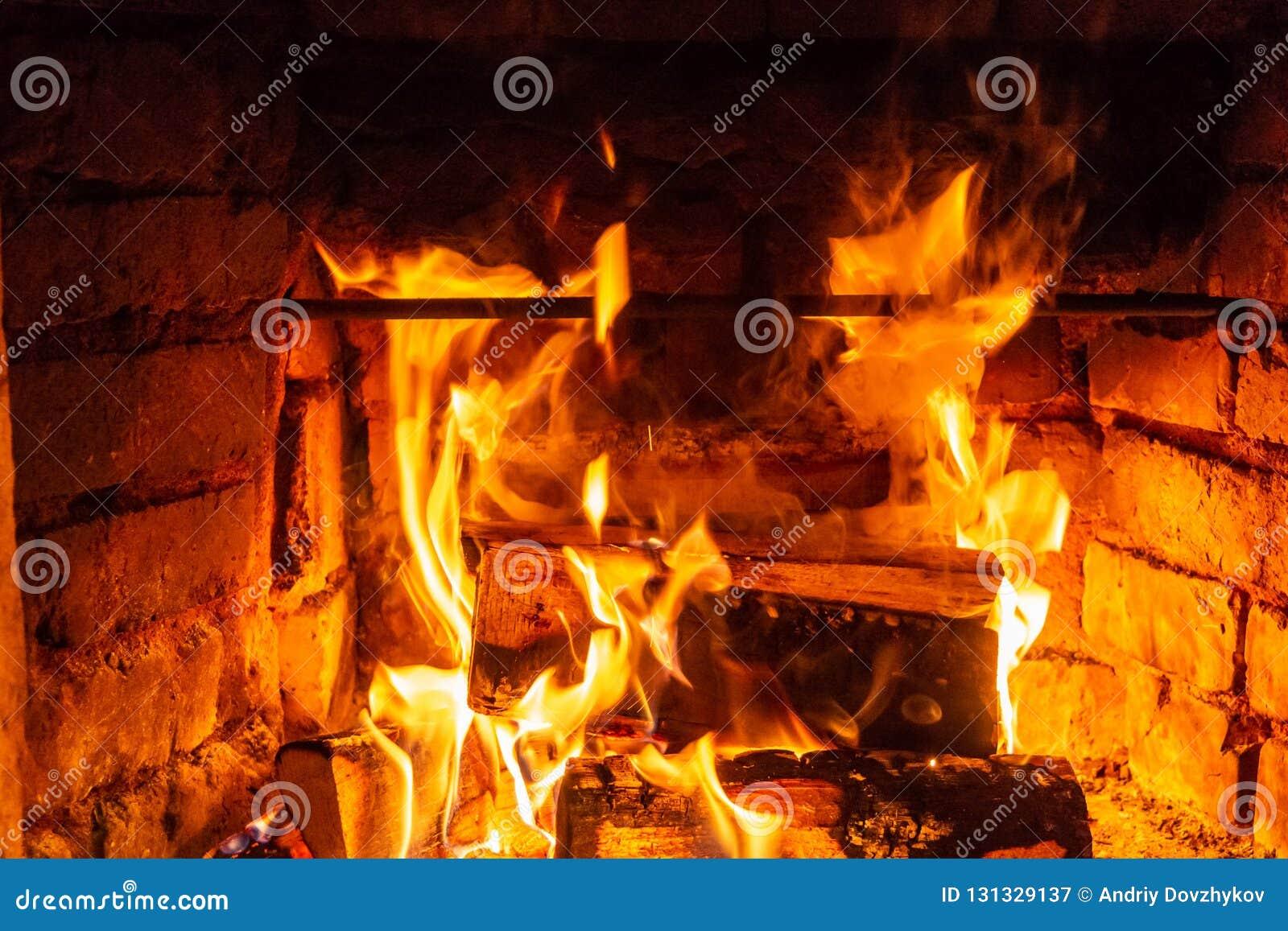 在火烧伤的木柴燃烧在壁炉 砖烤箱给热和热从被烧的日志 燃烧的煤炭和火焰