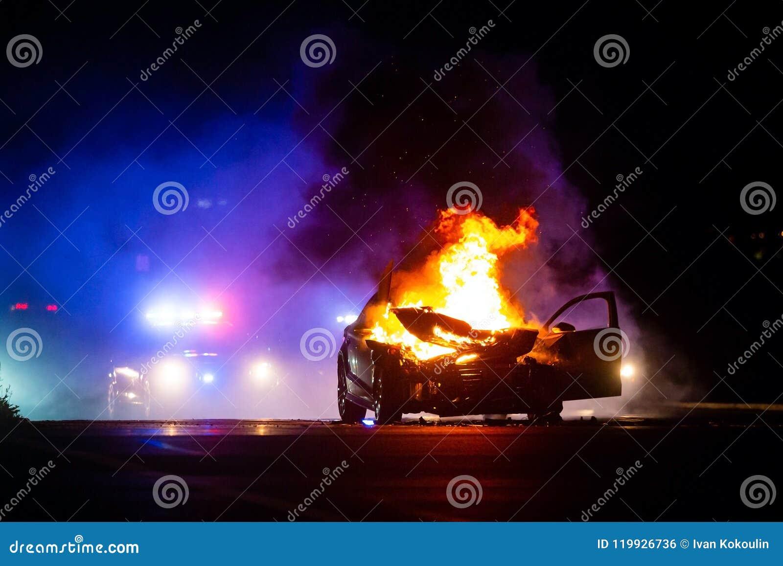 在火的汽车在与警察的晚上在背景中点燃