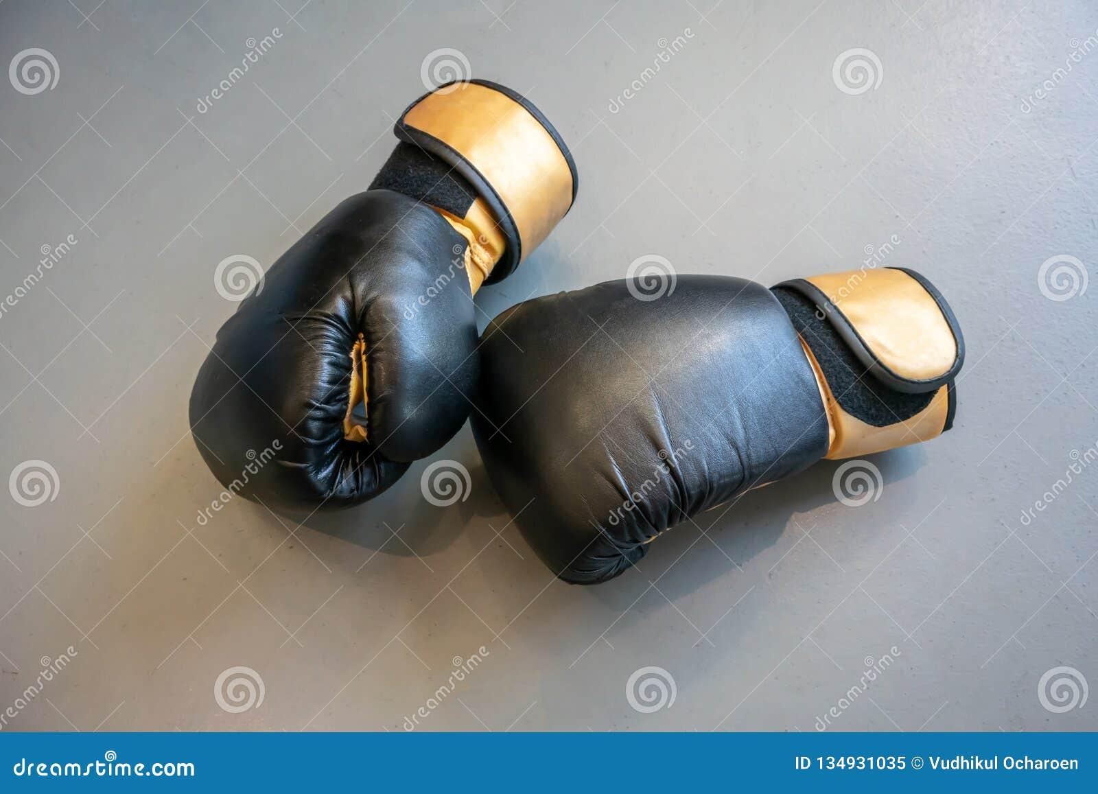 在灰色具体背景的老黑和黄色拳击手套