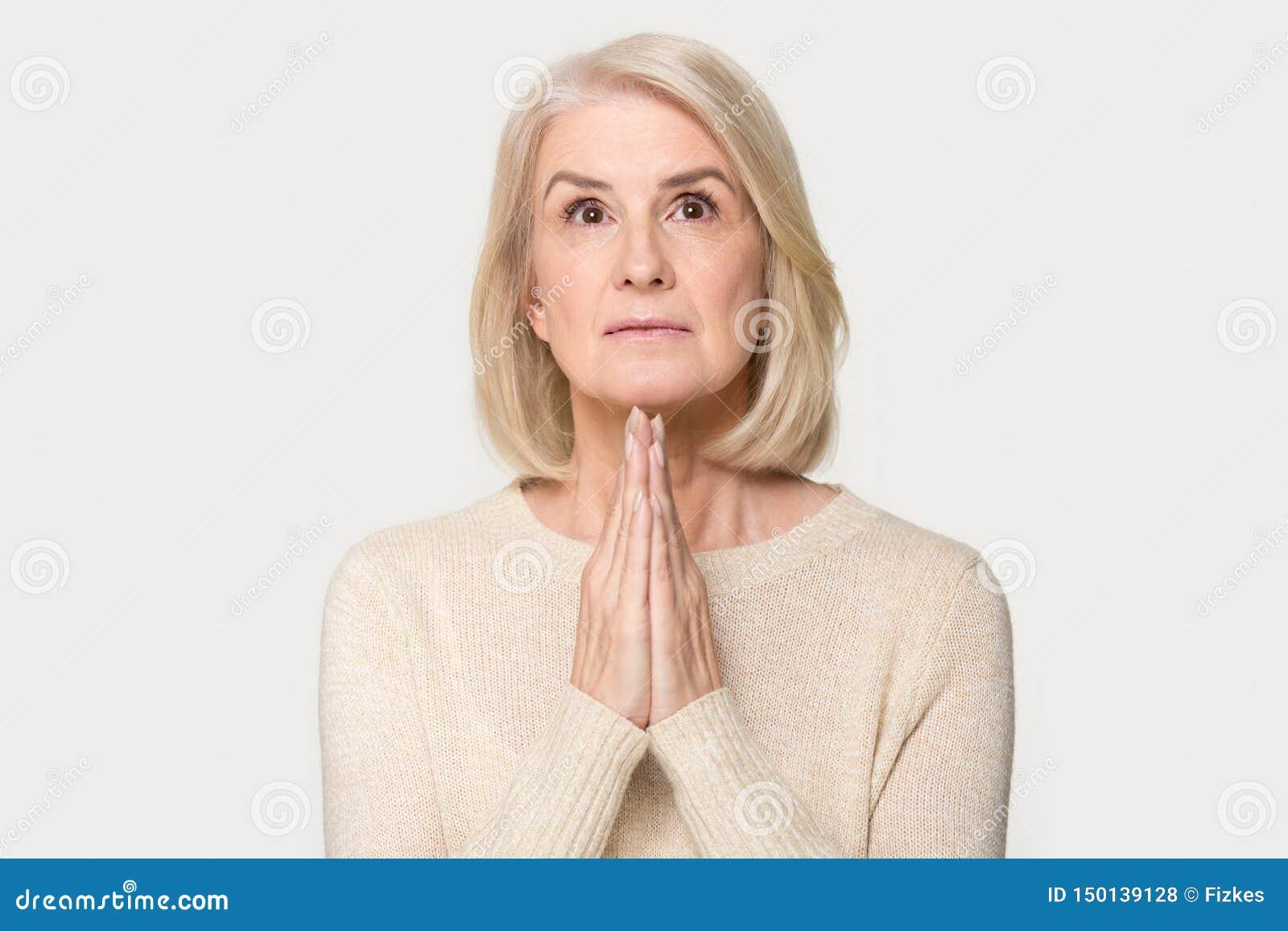 在灰色演播室背景隔绝的恳切年迈的妇女祈祷