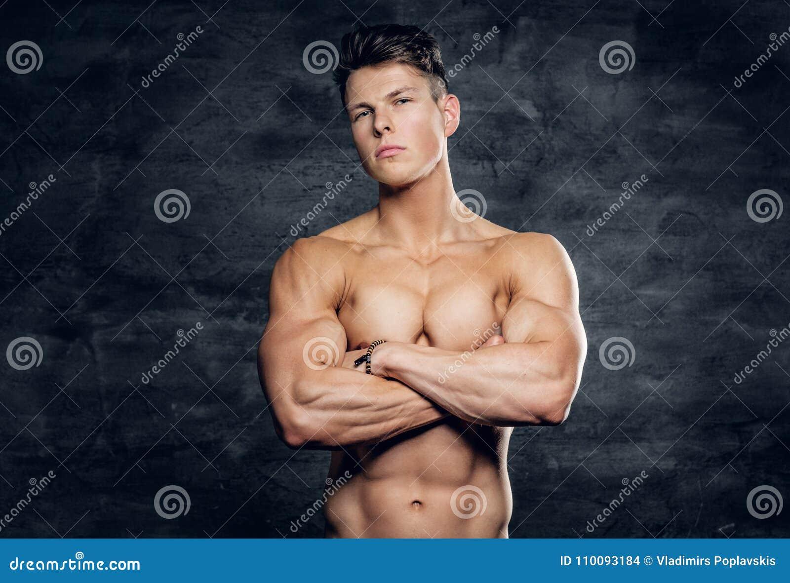在灰色背景的赤裸上身的运动的男性