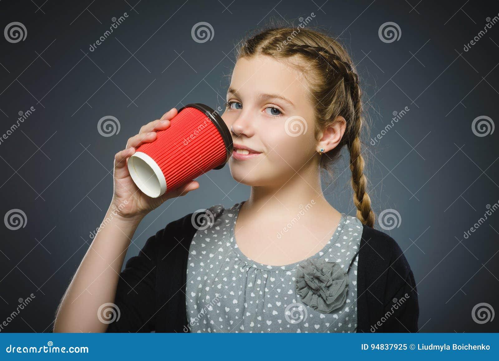 在灰色背景隔绝的十几岁的女孩饮料红色咖啡