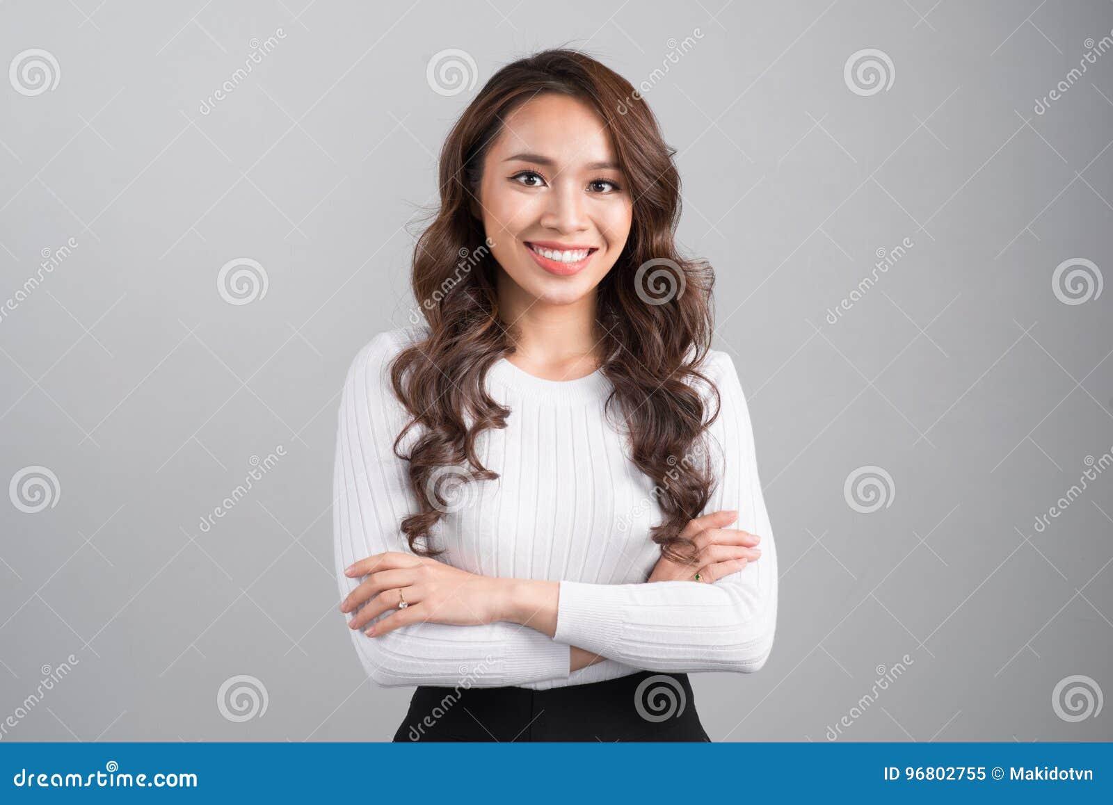 在灰色背景隔绝的微笑的确信的女实业家