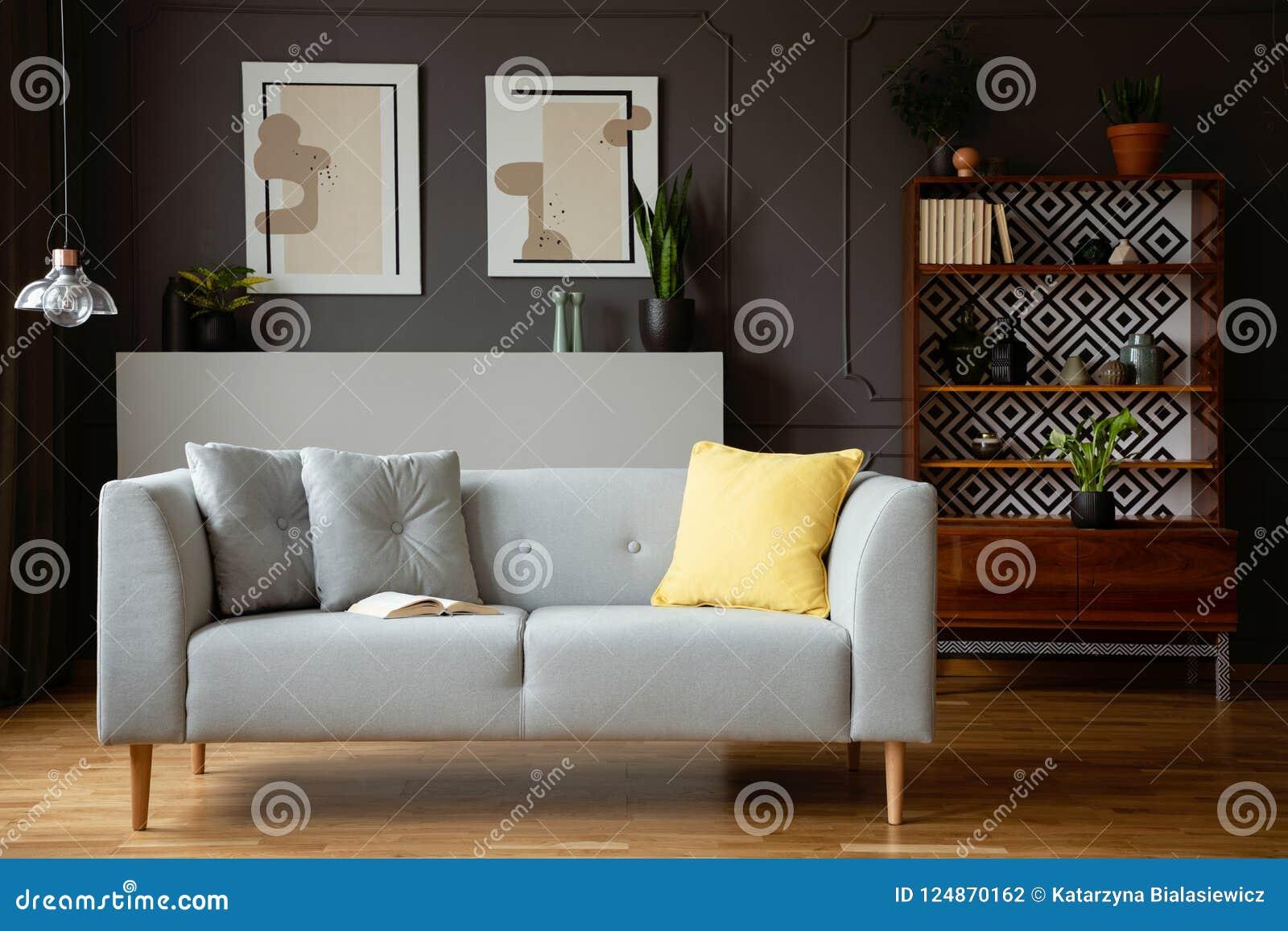 在灰色长沙发的黄色枕头在葡萄酒与灯和海报的客厅内部 实际照片