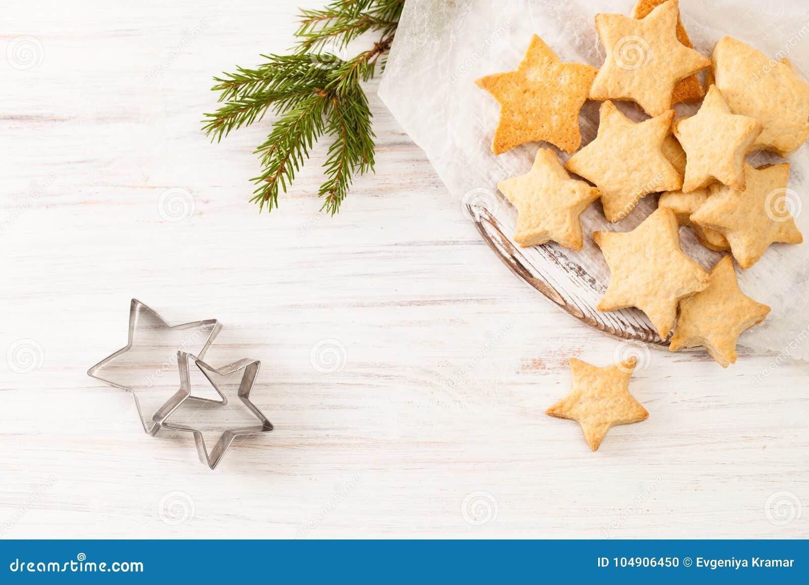 在烘烤纸的新鲜的被烘烤的饼干与冷杉在白色分支