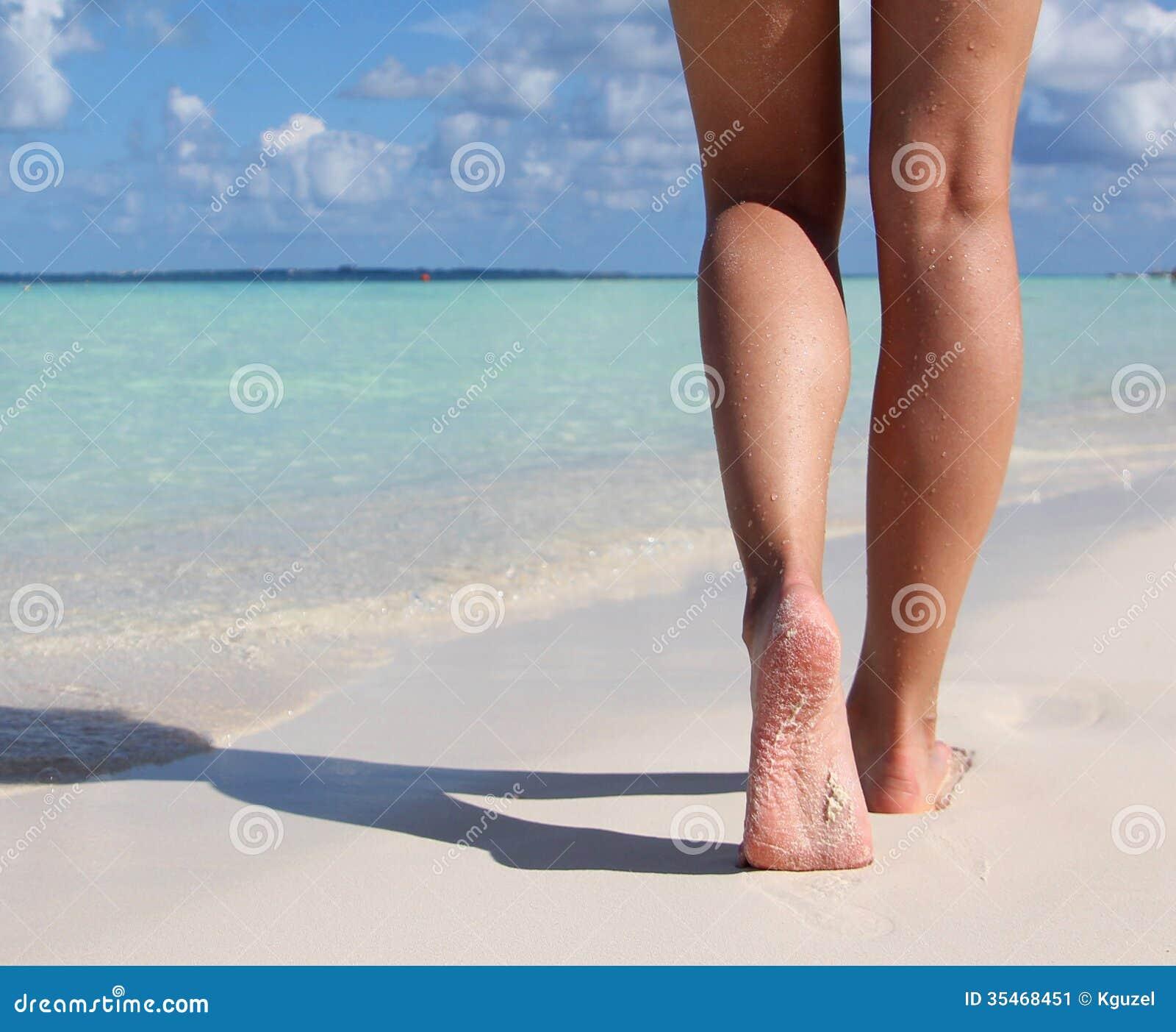 在热带沙子海滩的性感的腿。走的女性脚。