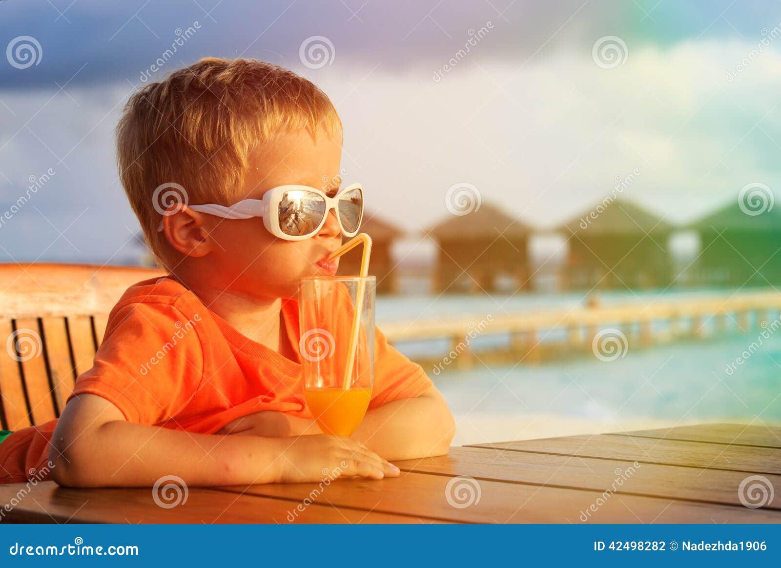 在热带海滩的小男孩饮用的鸡尾酒