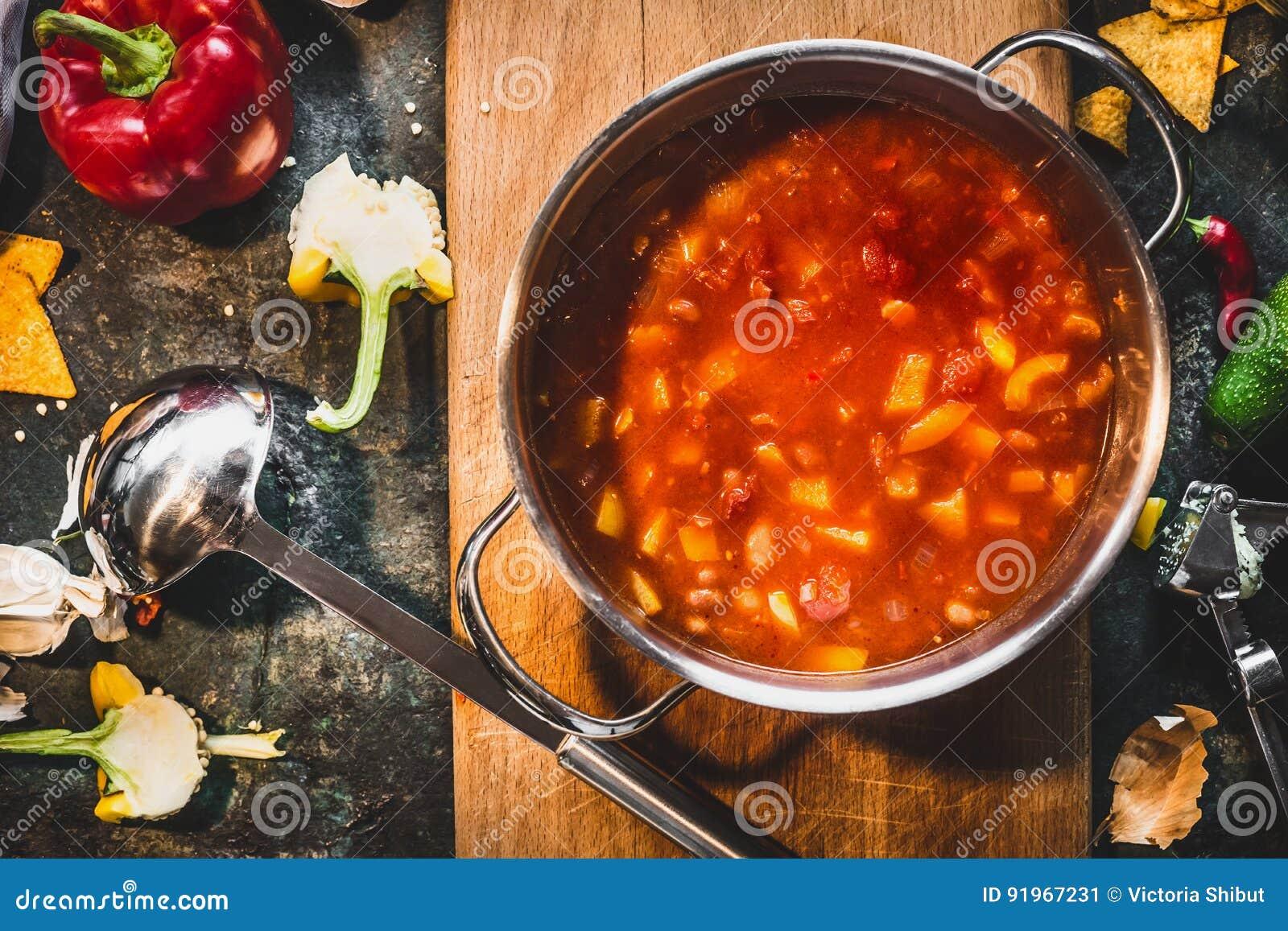 在烹调罐的热的墨西哥辣汤有在土气厨房用桌背景的杓子的