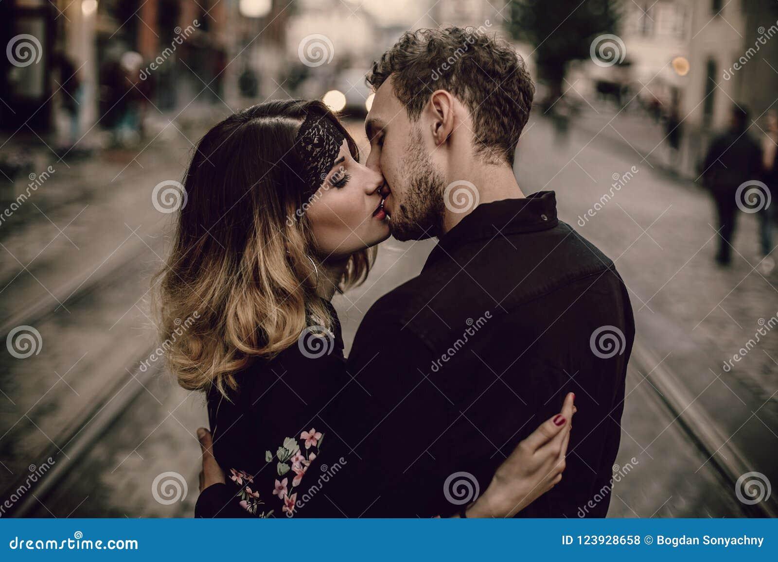 在爱亲吻的拥抱的时髦的吉普赛夫妇在晚上城市str