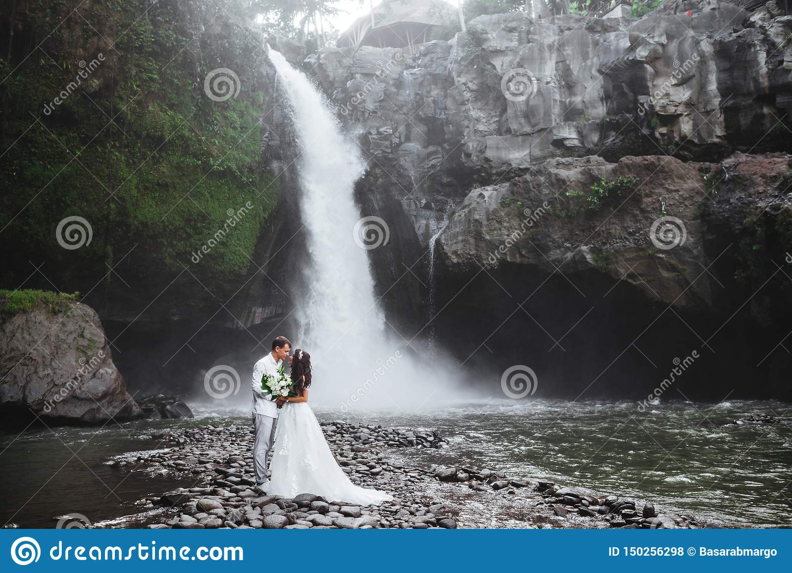 在爱新娘和新郎,在山瀑布附近的婚礼那天的年轻夫妇