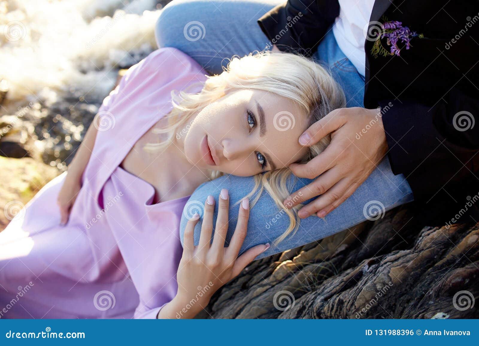 在爱特写镜头的夫妇坐一块石头在一美好的好日子在日落 爱情感和拥抱在阳光下 白肤金发的妇女