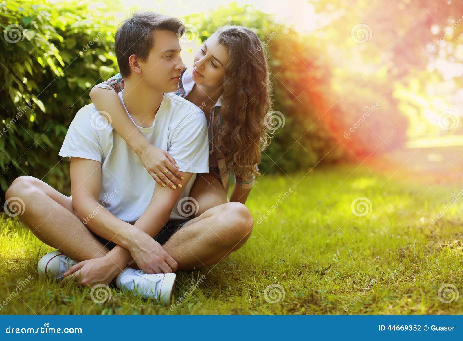 在爱的可爱的青少年夫妇获得在草坪的乐趣在公园