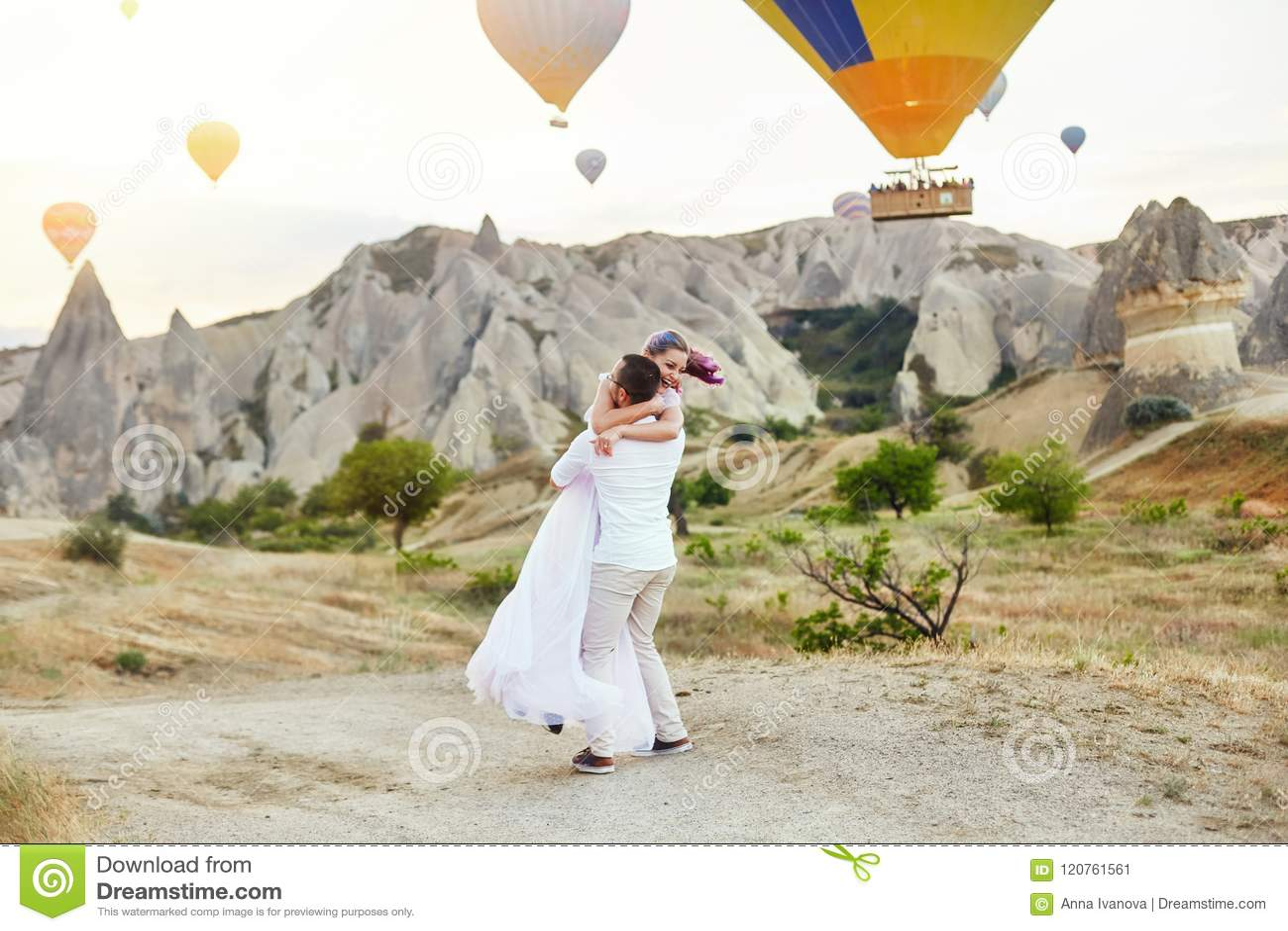 在爱的夫妇在气球背景站立在卡帕多细亚 供以人员和小山神色的一名妇女在很大数量的飞行气球