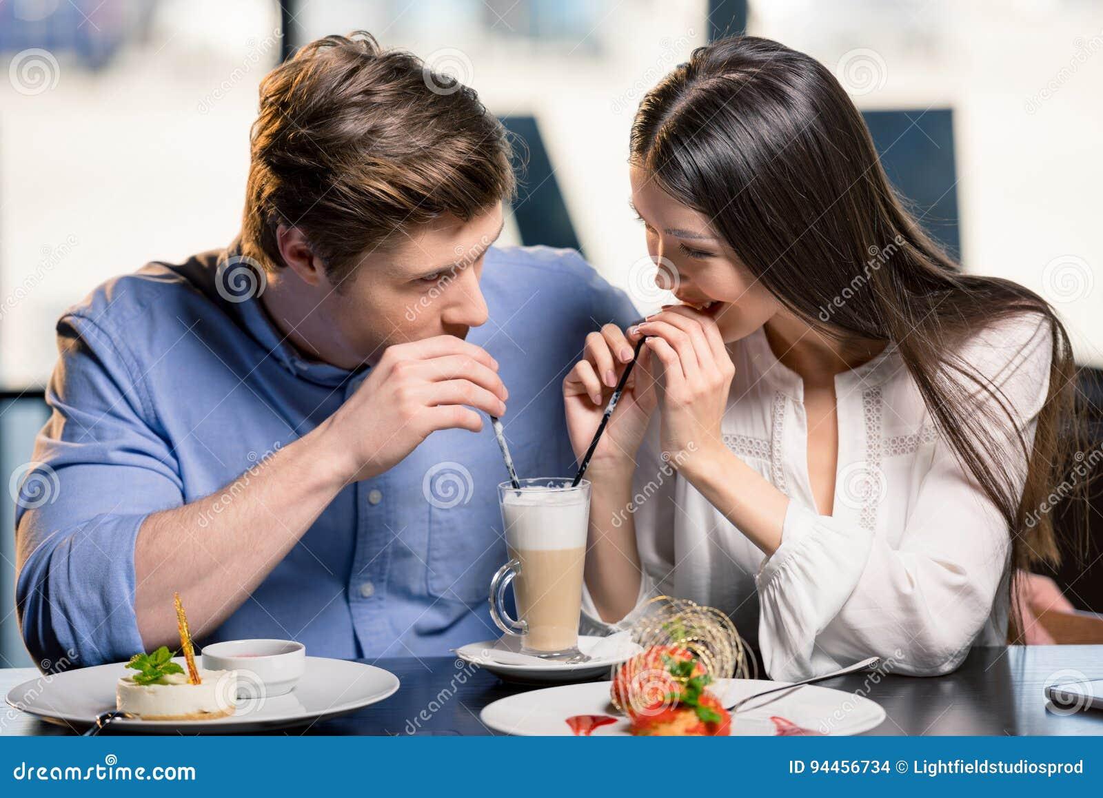 在爱的愉快的年轻夫妇在浪漫日期在餐馆