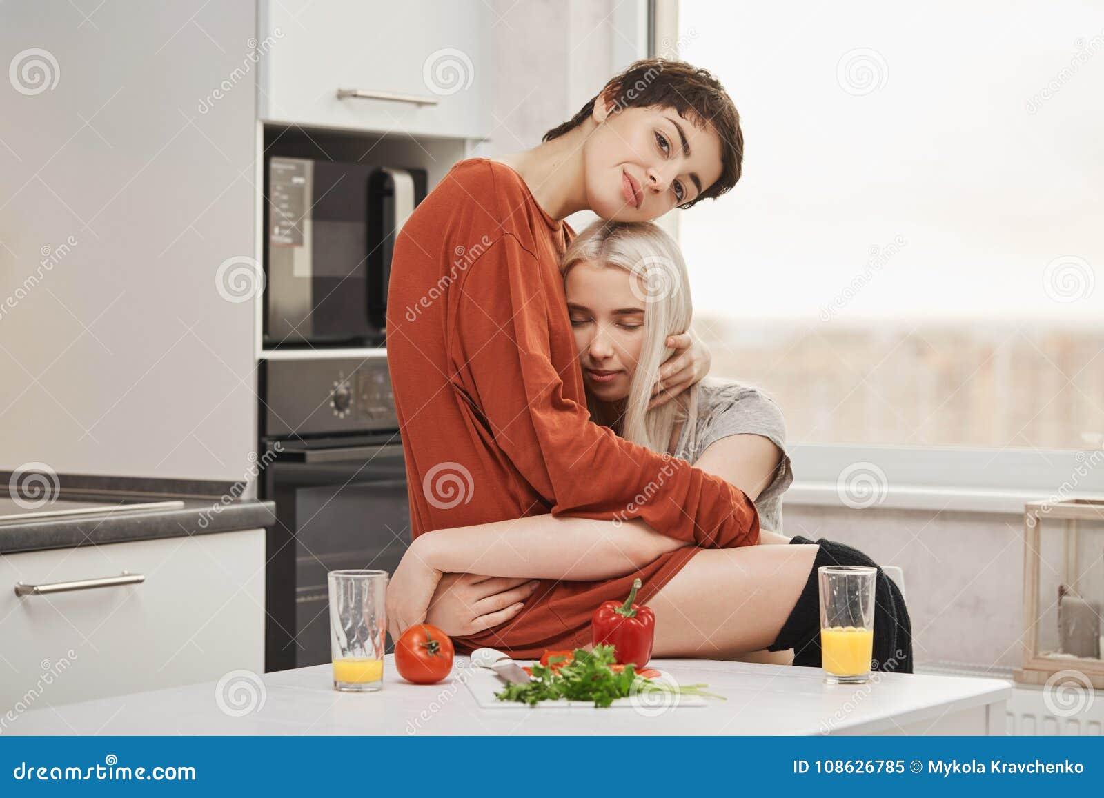 在爱的肉欲和嫩年轻女同性恋的夫妇,拥抱在厨房里,当吃早餐妇女时为每天是愉快的
