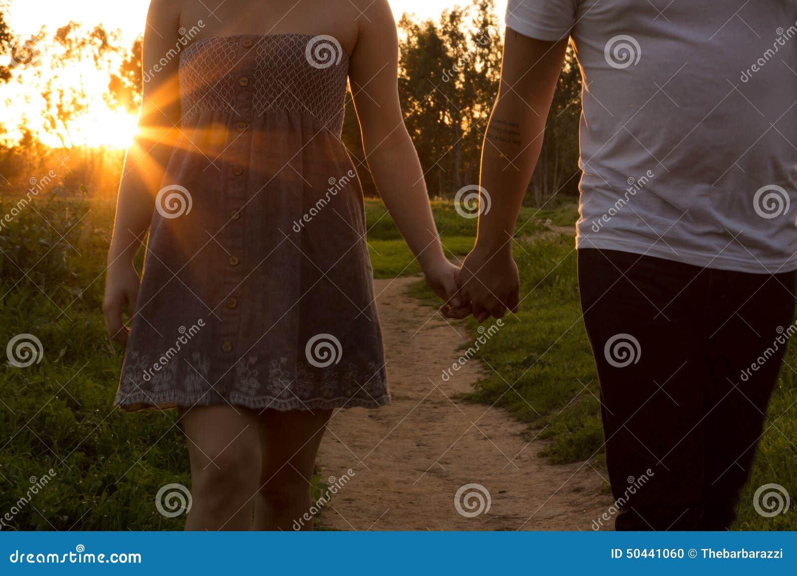 在爱的年轻夫妇在与太阳的一个领域通过树