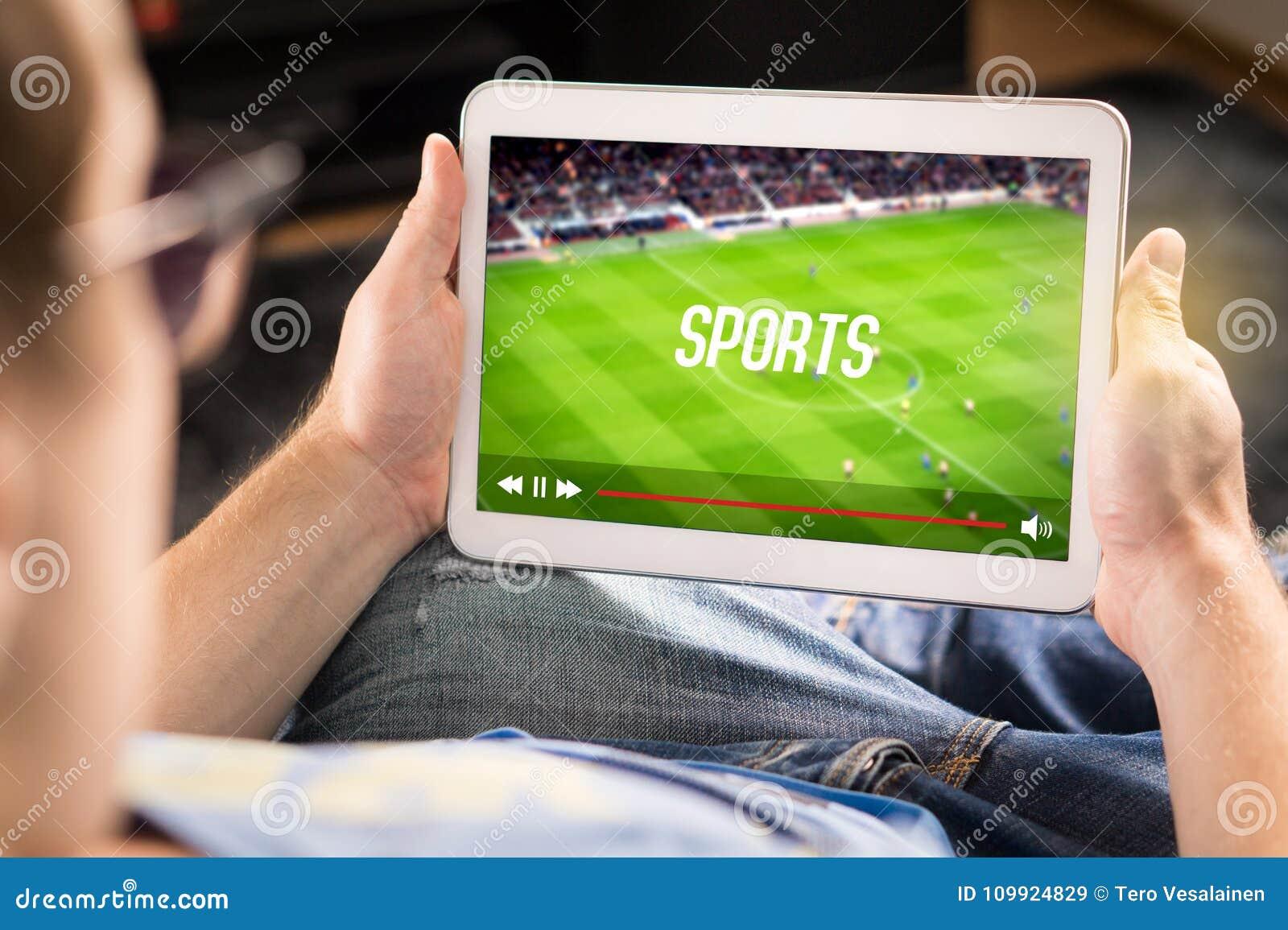 在片剂的人观看的体育 橄榄球和足球赛