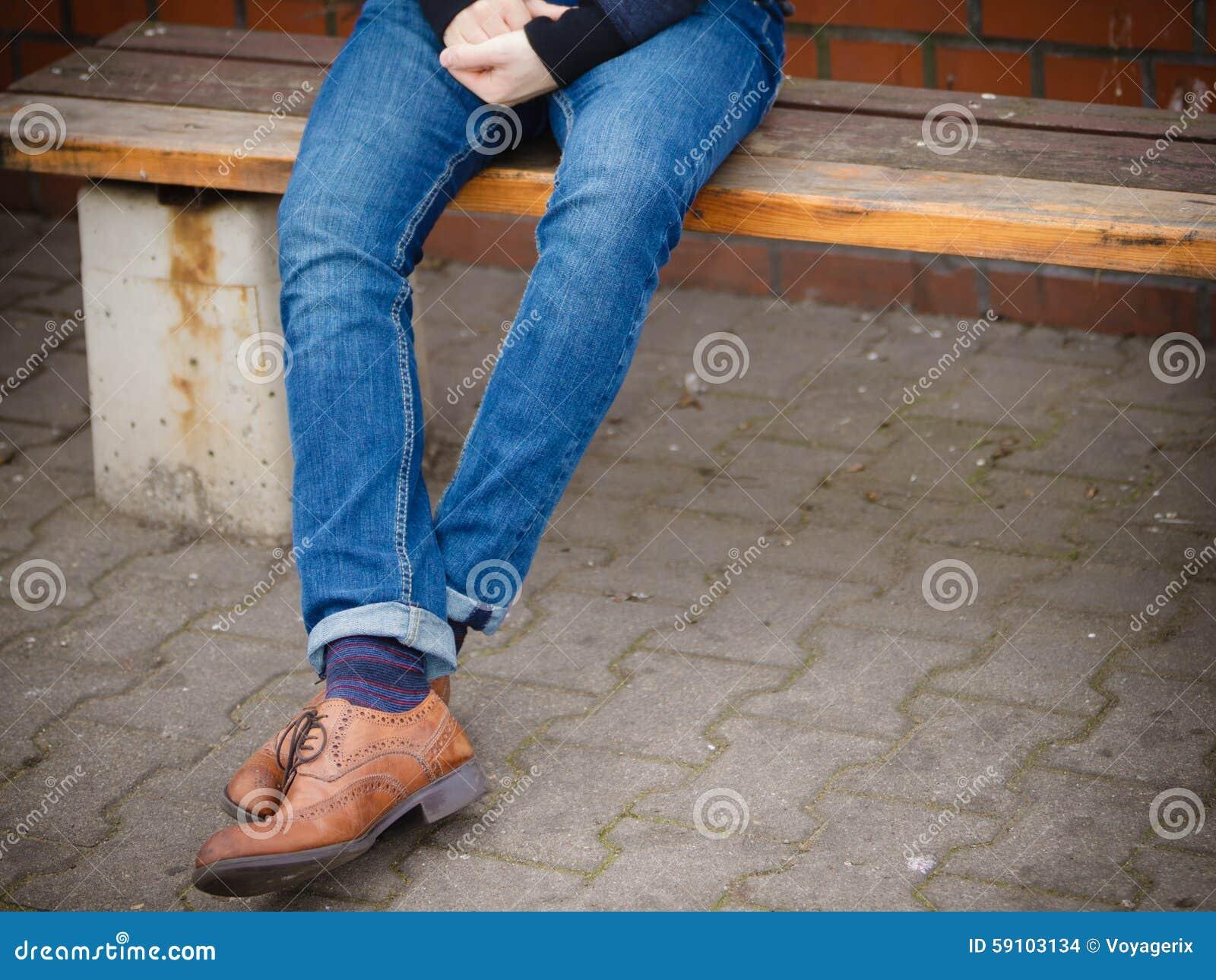 在牛仔裤和起动的男性腿