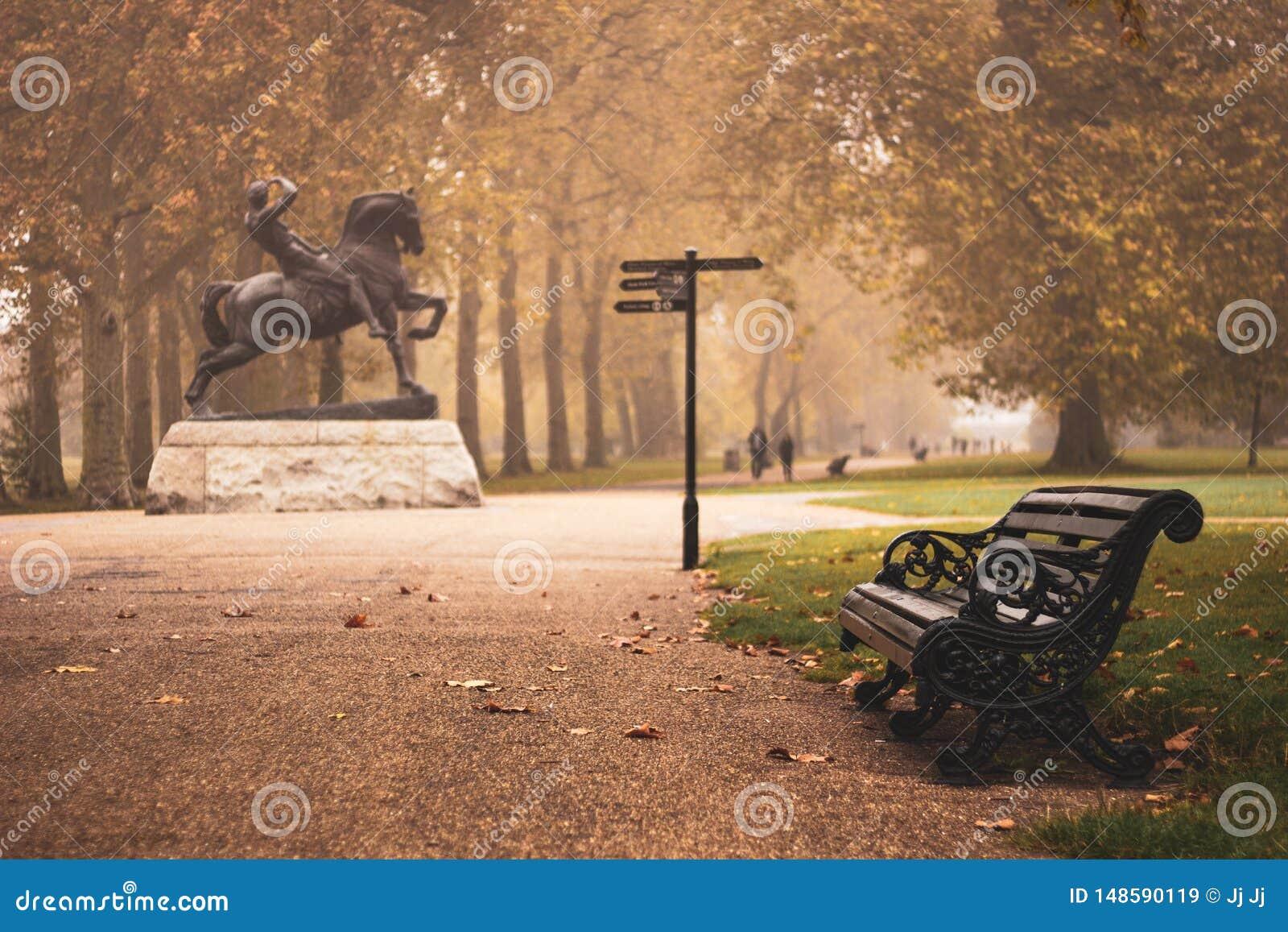 在物理能量雕象旁边的偏僻的长凳在海德公园 悲伤,忧郁,幽暗,寂寞