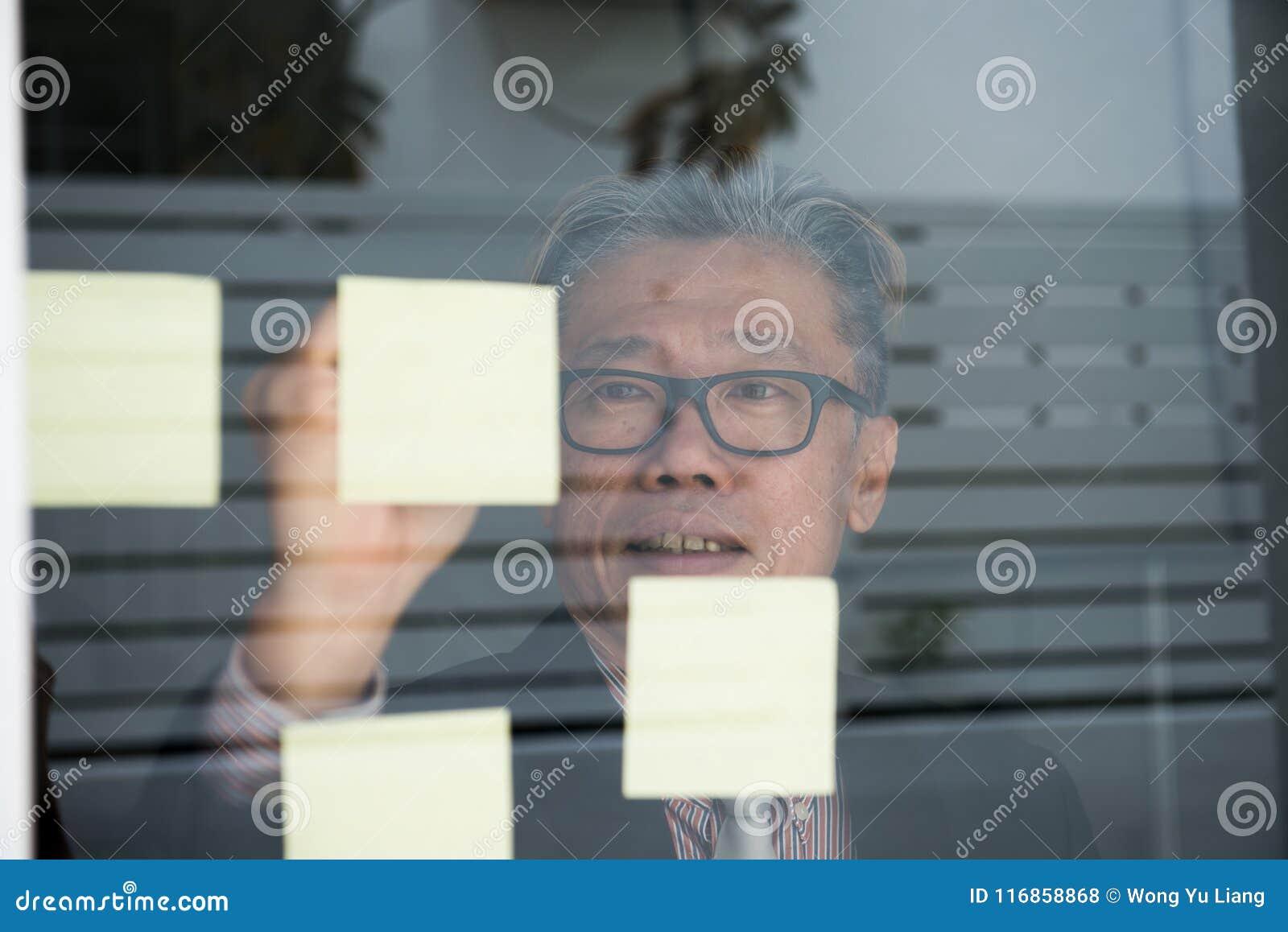 在玻璃墙上的亚洲商人文字