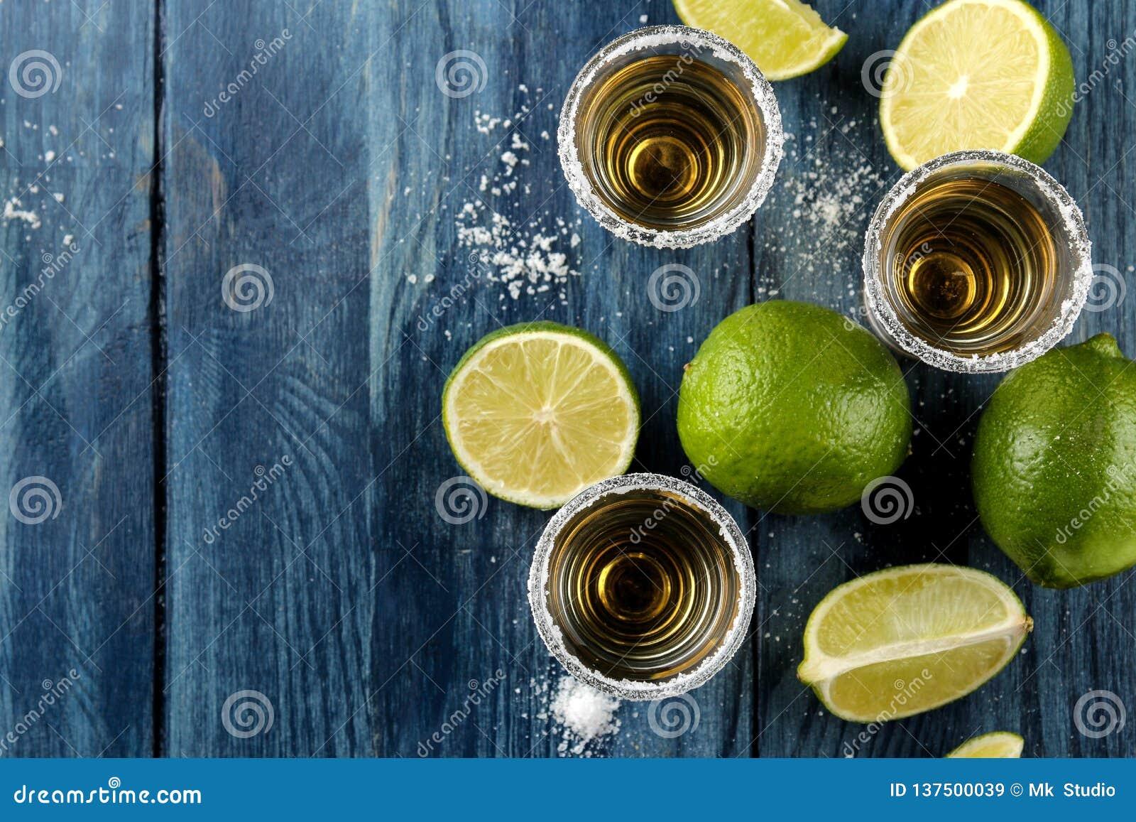 在玻璃玻璃的金子龙舌兰酒与盐和石灰在蓝色木背景 棒 酒精饮料 在视图之上 空间
