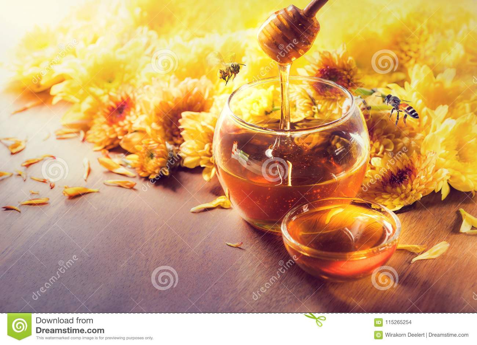 在玻璃瓶子的蜂蜜有蜂飞行和花的在一个木地板上