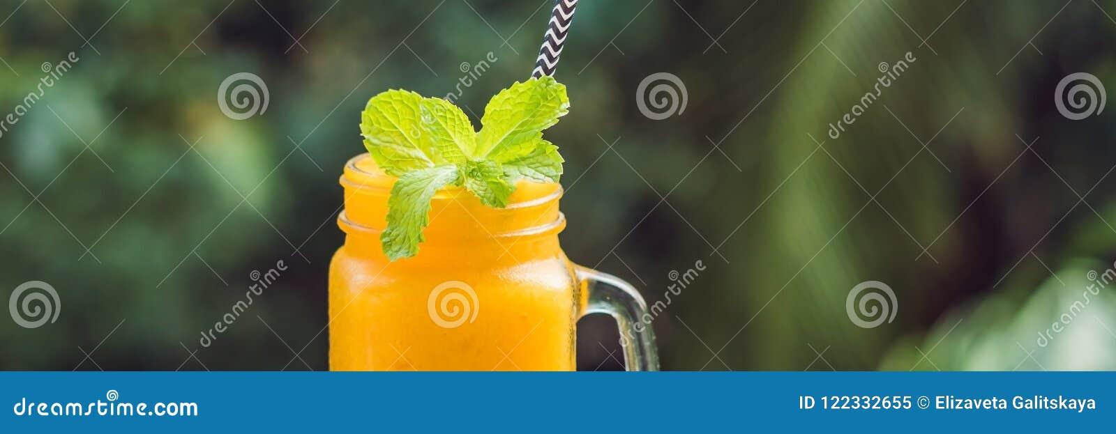 在玻璃金属螺盖玻璃瓶和芒果的芒果圆滑的人在绿色背景 芒果震动 热带水果概念横幅,长的格式