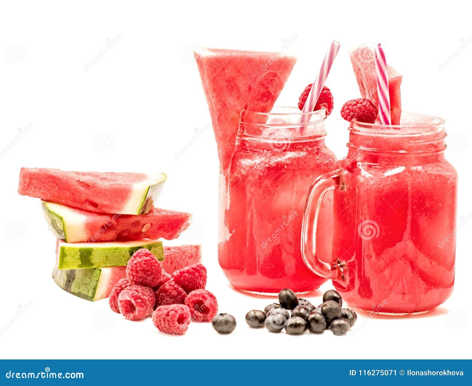 在用切片装饰的金属螺盖玻璃瓶的西瓜圆滑的人西瓜、莓、蓝莓和在白色隔绝的冰块