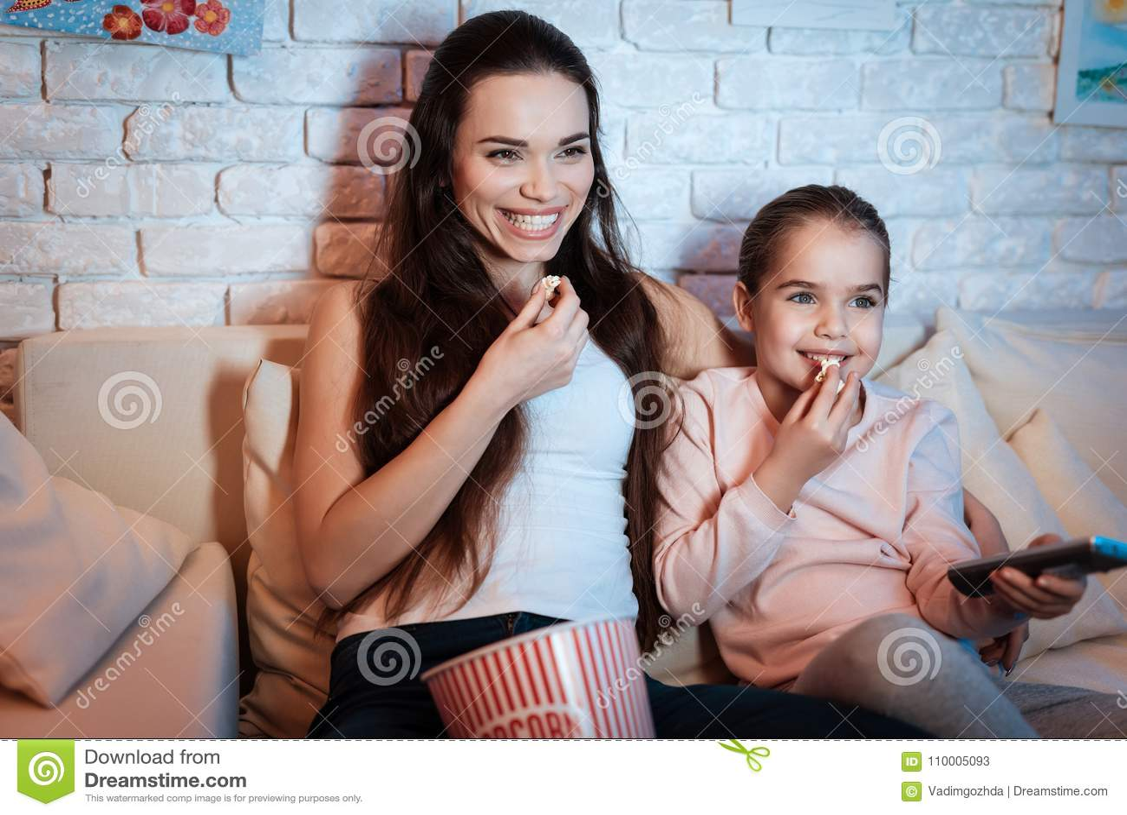 在电视上的母亲和女儿观看的电影在晚上在家