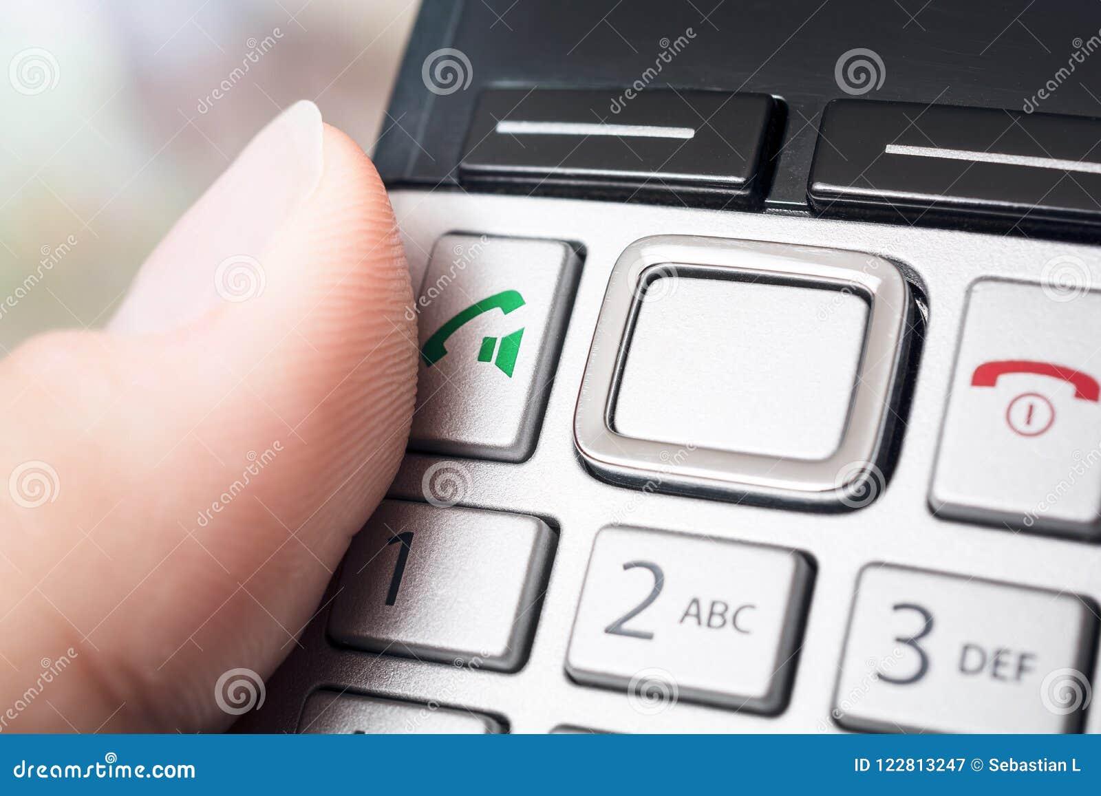 在电话按钮的男性手指无线DECT Telefphone,准备拨或激活扬声麦克风作用