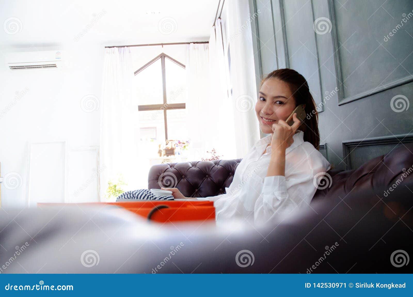 在电话的妇女微笑和谈话