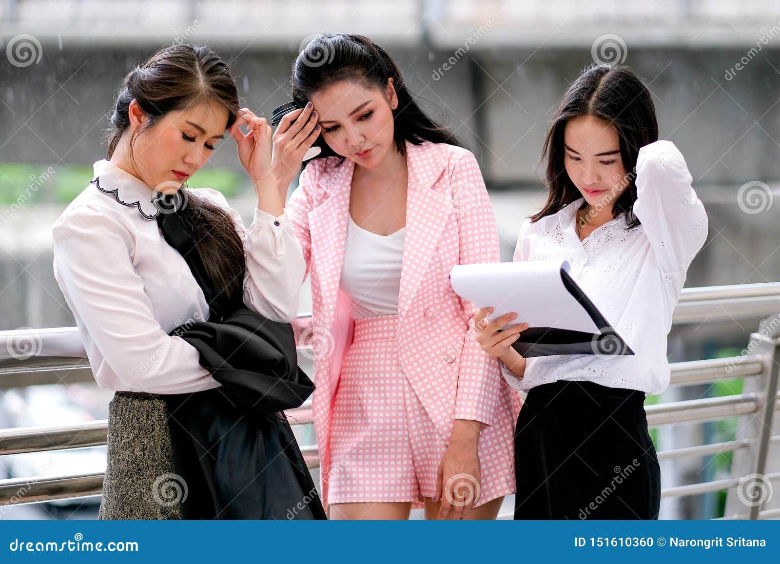 在白天在办公室外,三个企业亚裔女孩作为不快乐和严重关于他们的工作