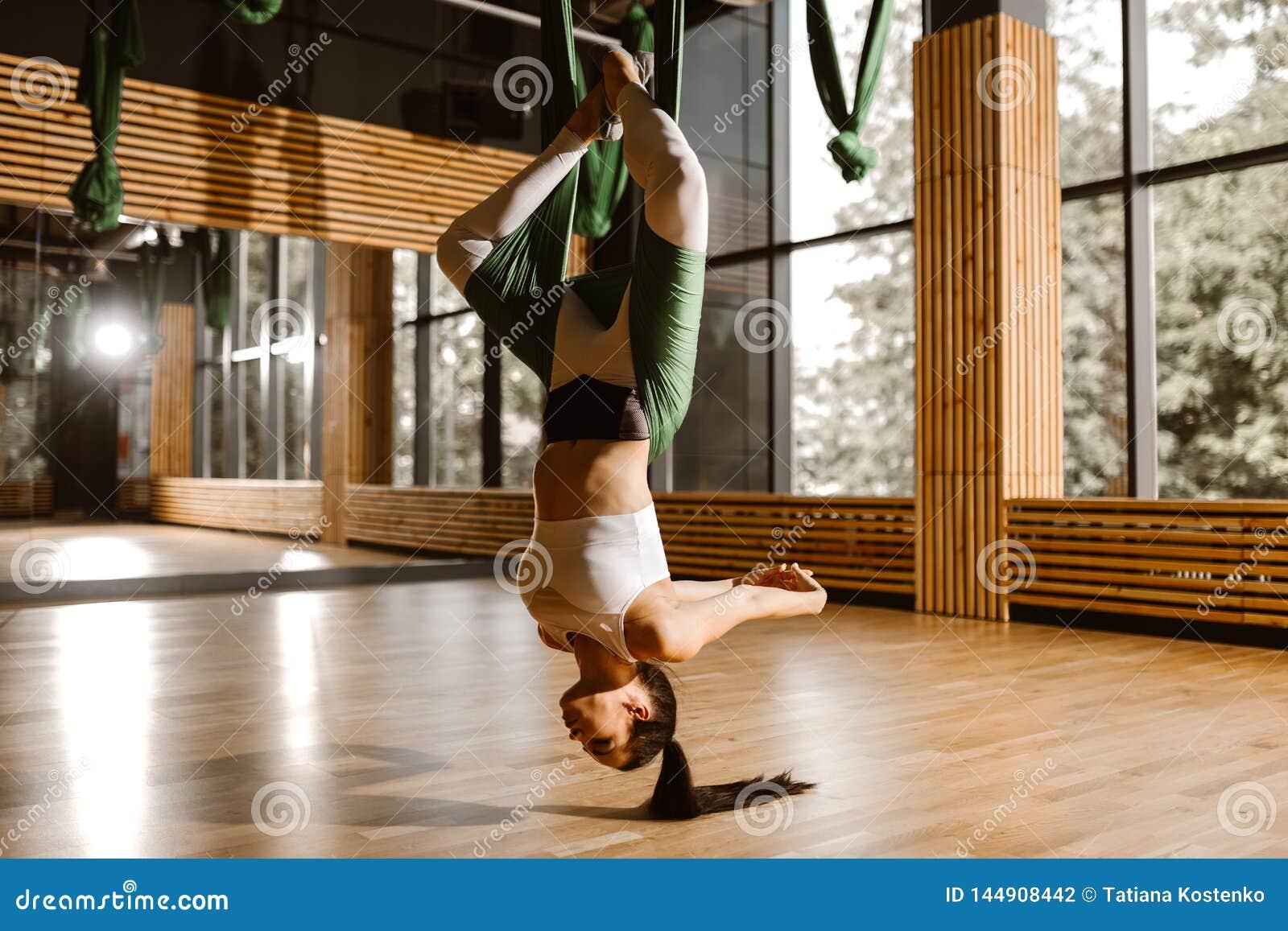在白色体育上面和贴身衬衣打扮的年轻亭亭玉立的深色头发的女孩做着在绿色吊床的瑜伽