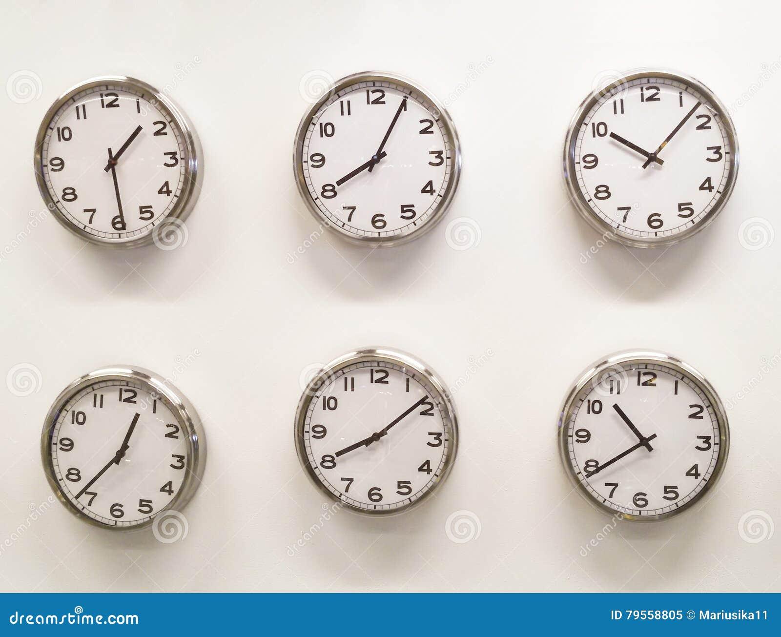 在白色墙壁上的六个时钟